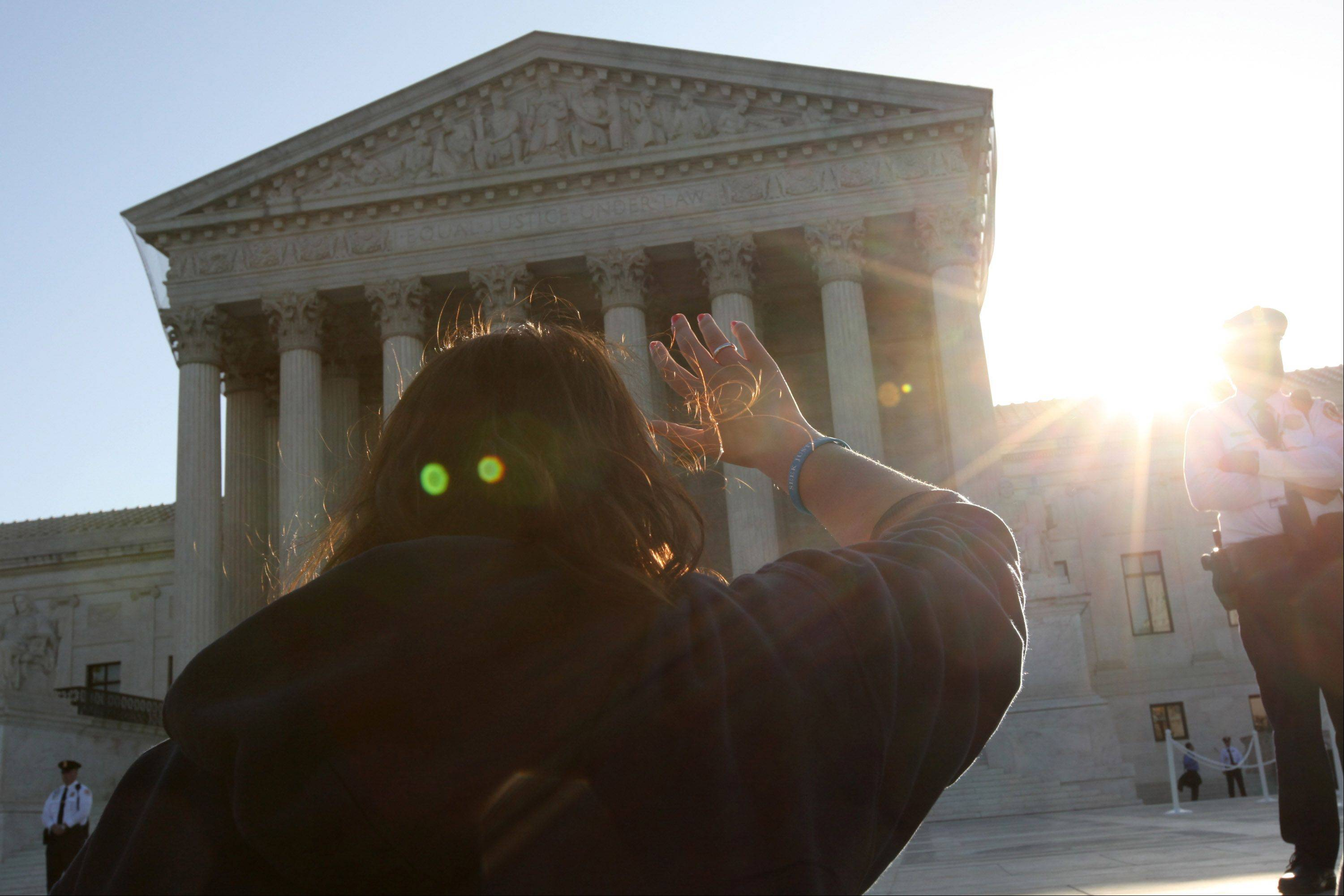 A demonstrator prays outside the Supreme Court building in Washington, D.C., U.S., on Monday, March 26, 2012. The Supreme Court opens today its historic review of President Barack Obama's health-care law, three days of arguments that might result in the president's premier legislative achievement being found unconstitutional in the middle of his re-election campaign.