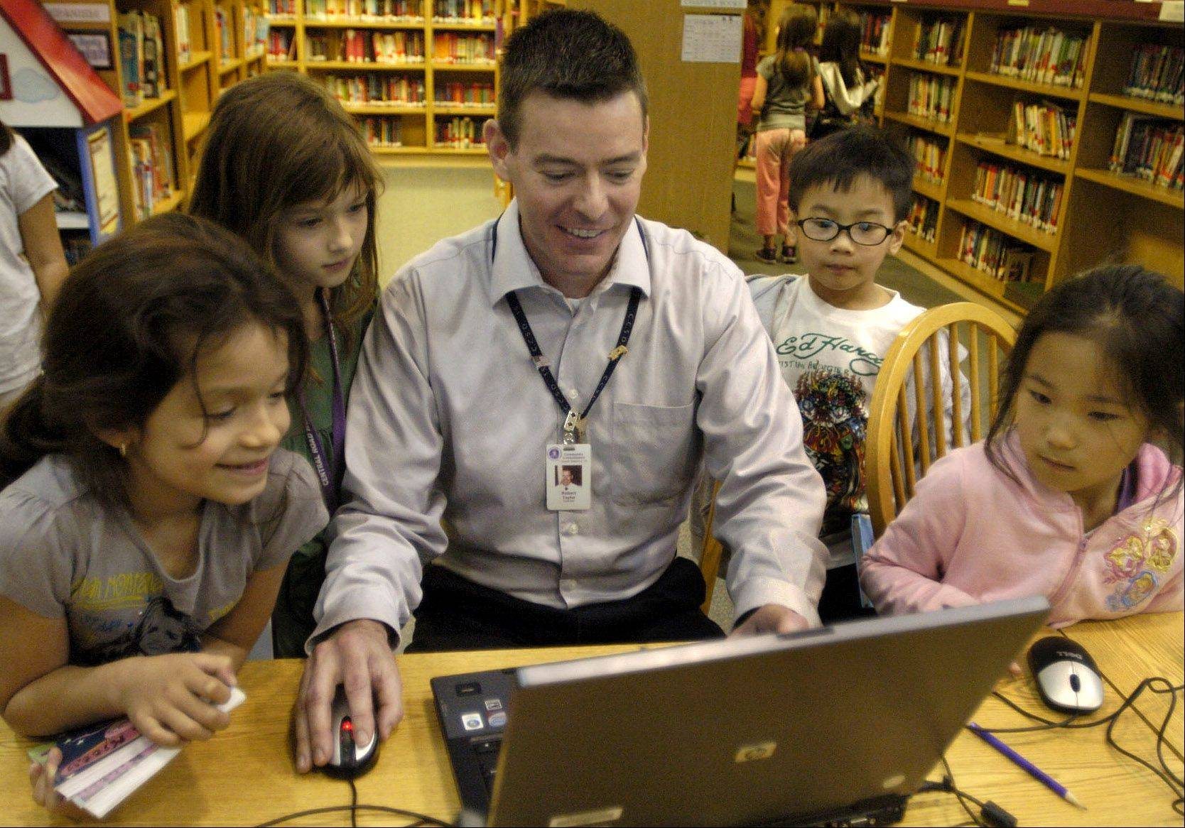 Golden Apple finalist second-grade teacher Rob Taylor at Central Road School in Rolling Meadows shows students, from left, Adriana Hurtado, Ella Gray, Hao Duong and Jessica Sun an integrated lesson involving biographies that incorporate research, writing, public speaking and art.