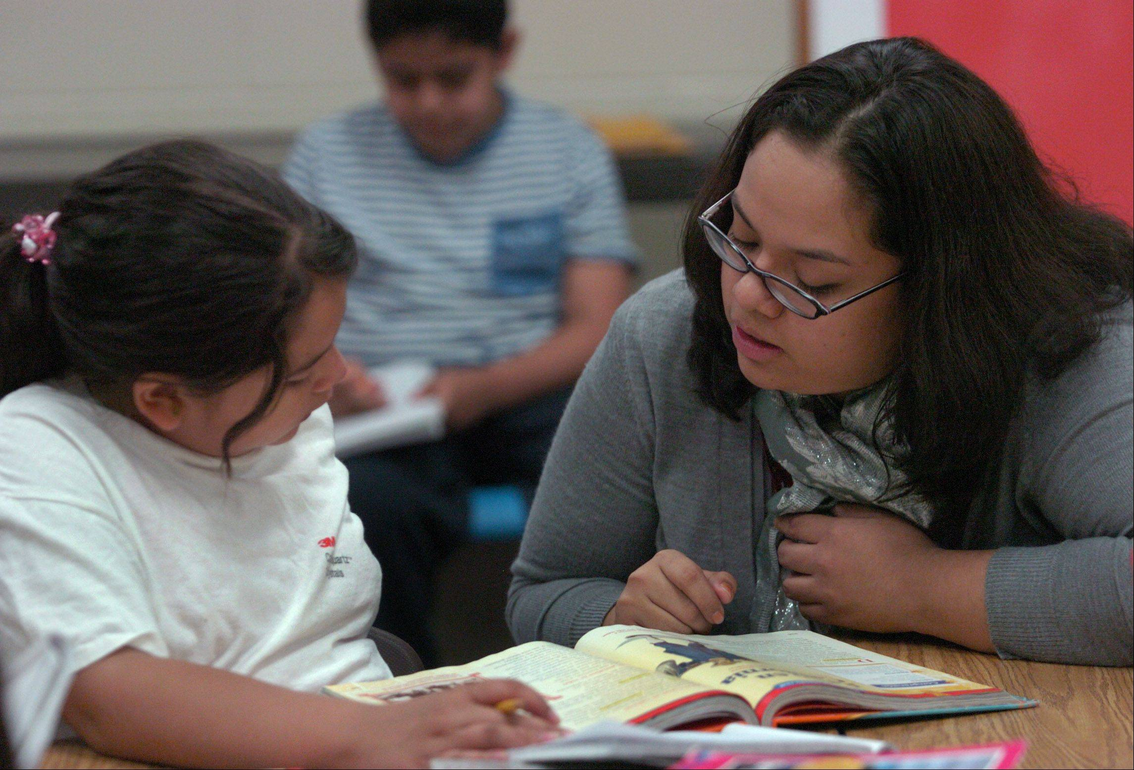Golden Apple finalist third grade dual-language teacher Maria Barba, works with one of her students, Gloria Arellano, at MacArthur School in Hoffman Estates.
