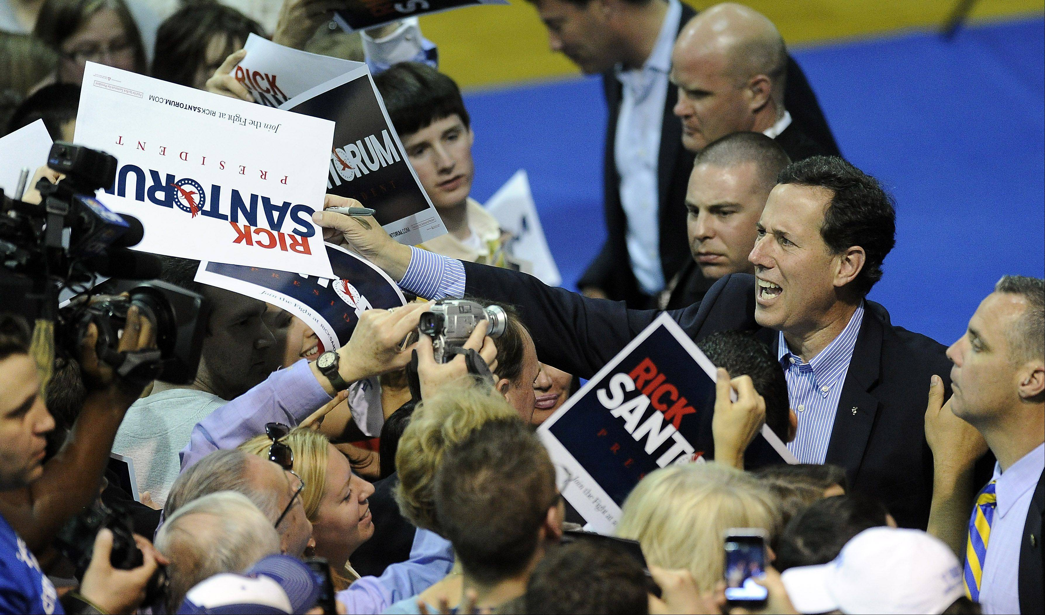 Rick Santorum signs autographs after his campaign rally at Christian Liberty Academy in Arlington Heights on Friday.