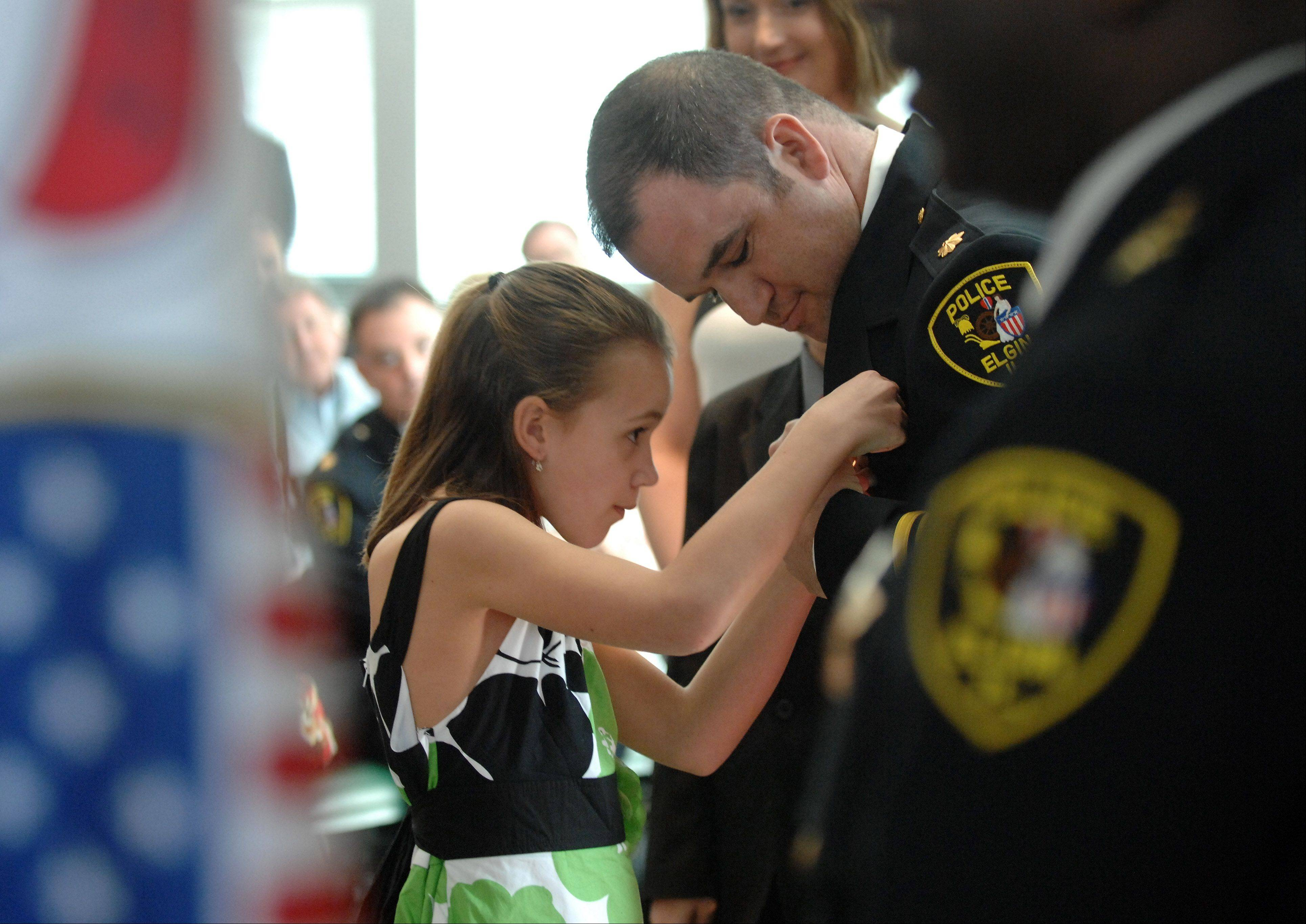 Newly sworn-in Commander Glenn Theriault watches as his daughter Katie, 9, pins on his new badge during a promotion and retirement ceremony for the Elgin Police Department Friday.