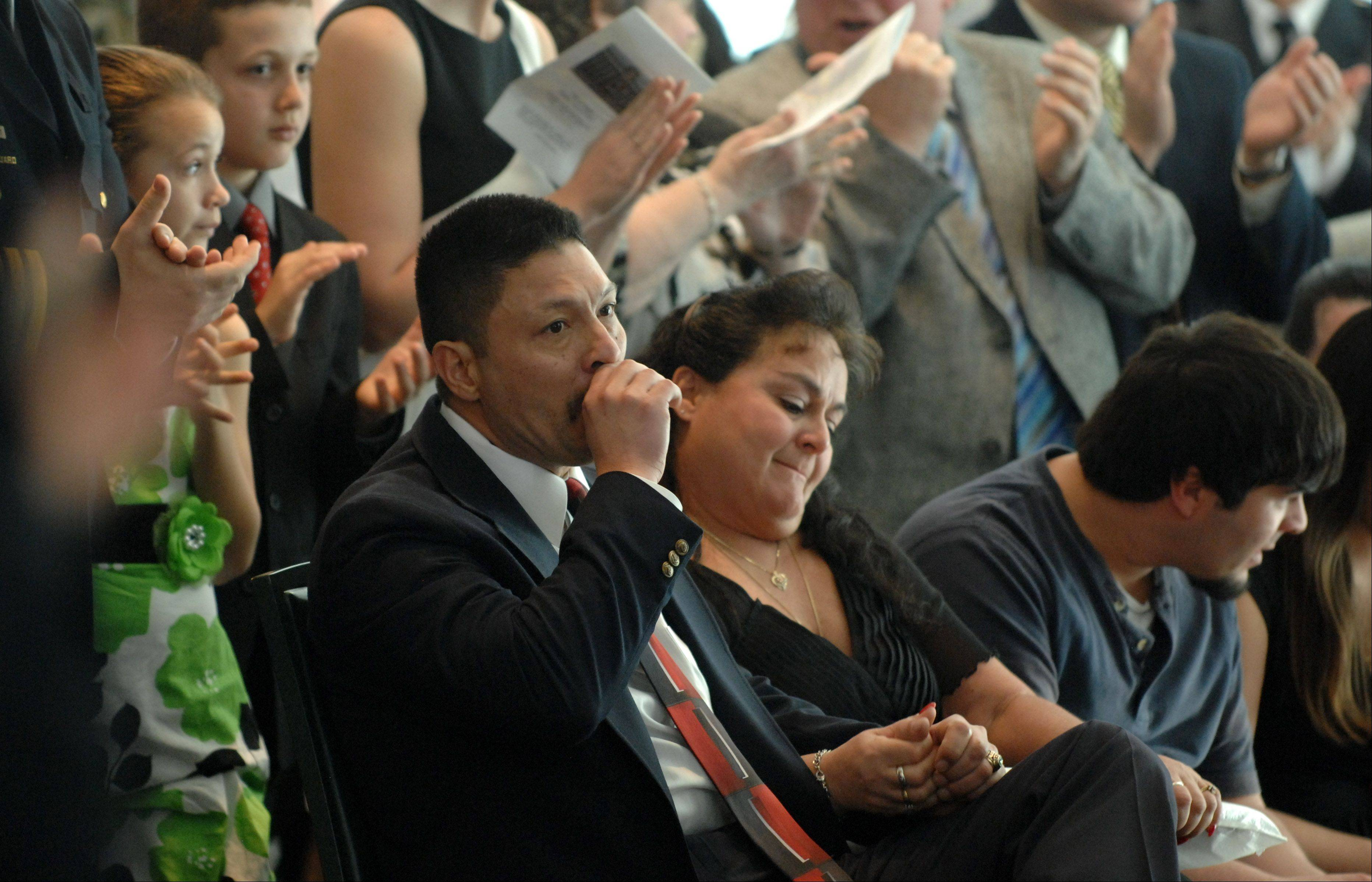 Sergeant Jose Morales gets emotional after his retirement speech as he sits with his family to a standing ovation during a promotion and retirement ceremony for the Elgin Police Department Friday.