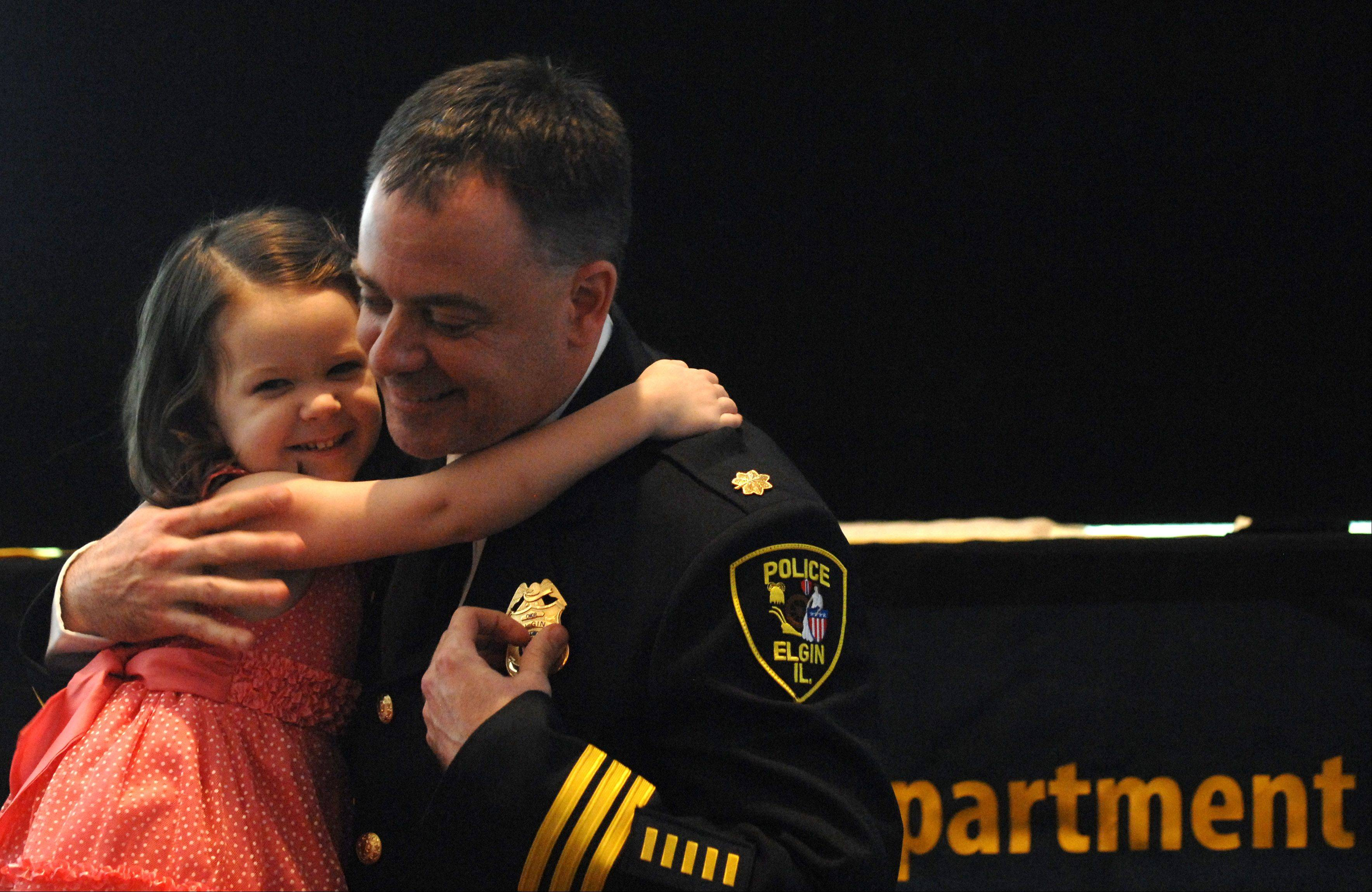 Bill Wolf gets a hug from his daughter Abby, 3, after she pinned on his badge just after he was the first person sworn in to the rank of Commander during a promotion and retirement ceremony for the Elgin Police Department Friday.