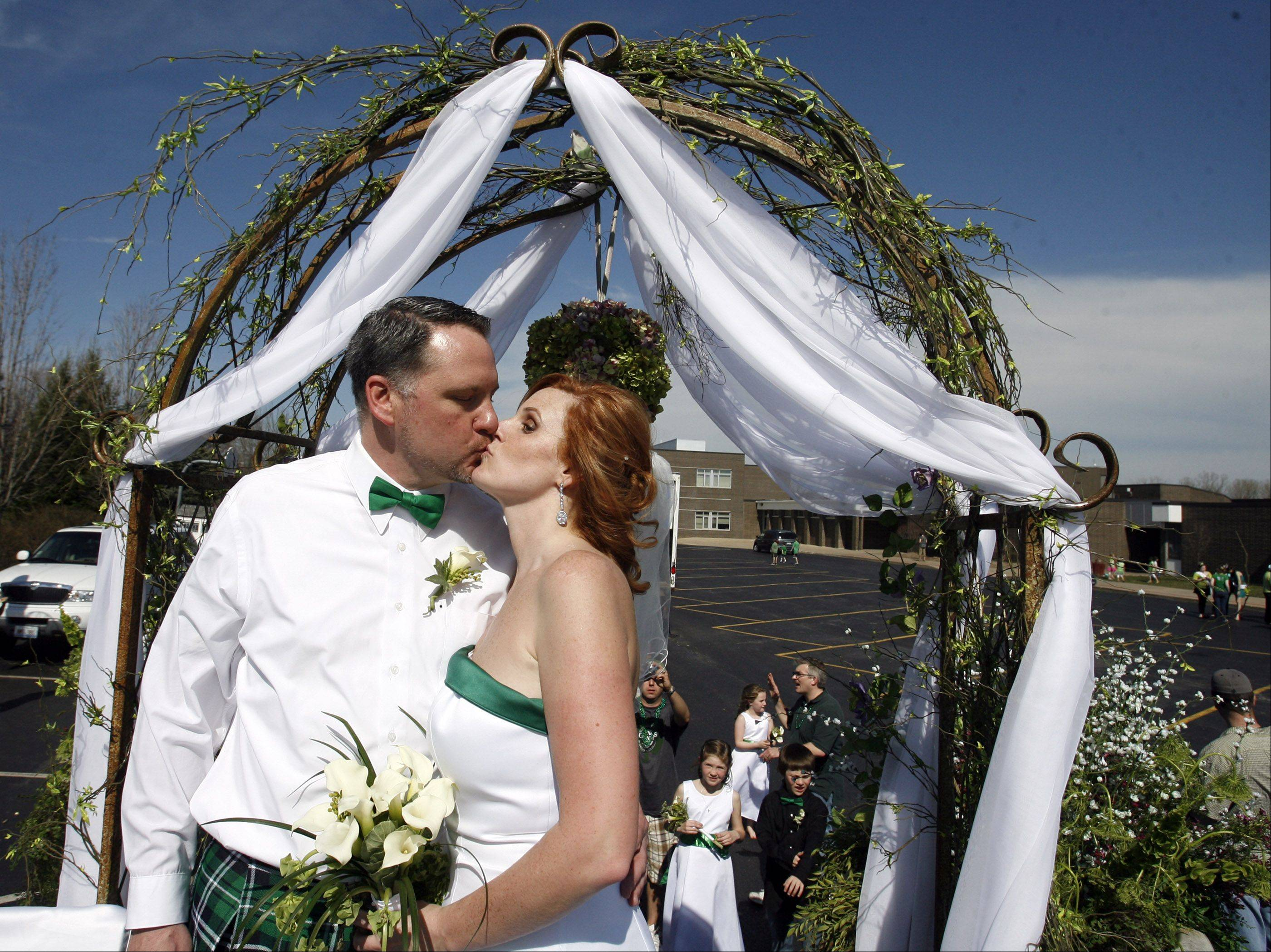 Tara Teschky and Paul Quinn of Libertyville kiss after getting married on a float during the Lake Villa St. Patrick's Day parade on Saturday, March 17th.