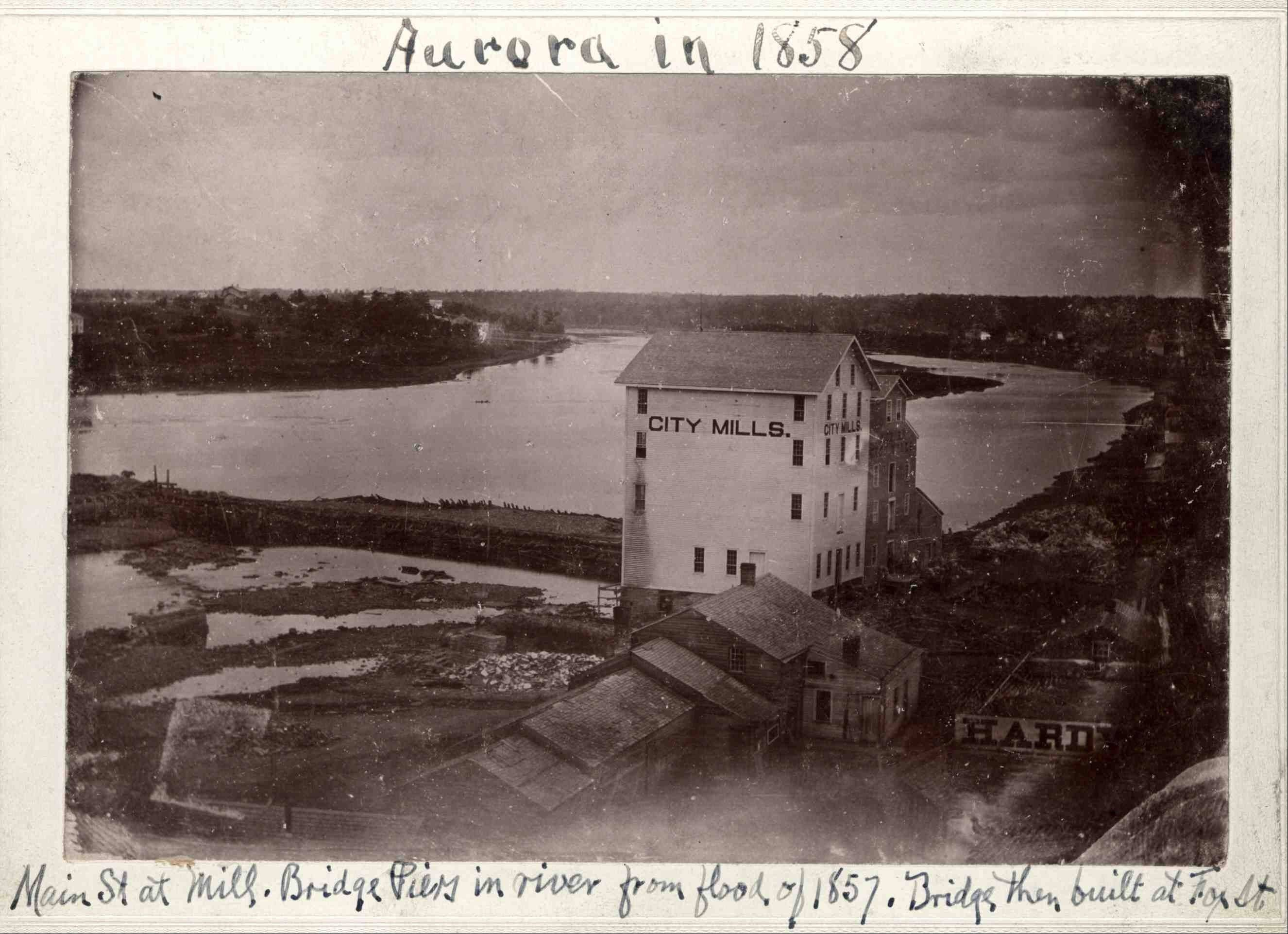 This picture of McCarty's mills was taken in 1858, more than 20 years after their construction. The dark building to the rear was the sawmill, built in 1834-35; the white building in front was the grist mill, built in 1836-37. The buildings were on the east bank of the river, on the north side of what is today East Galena Boulevard.