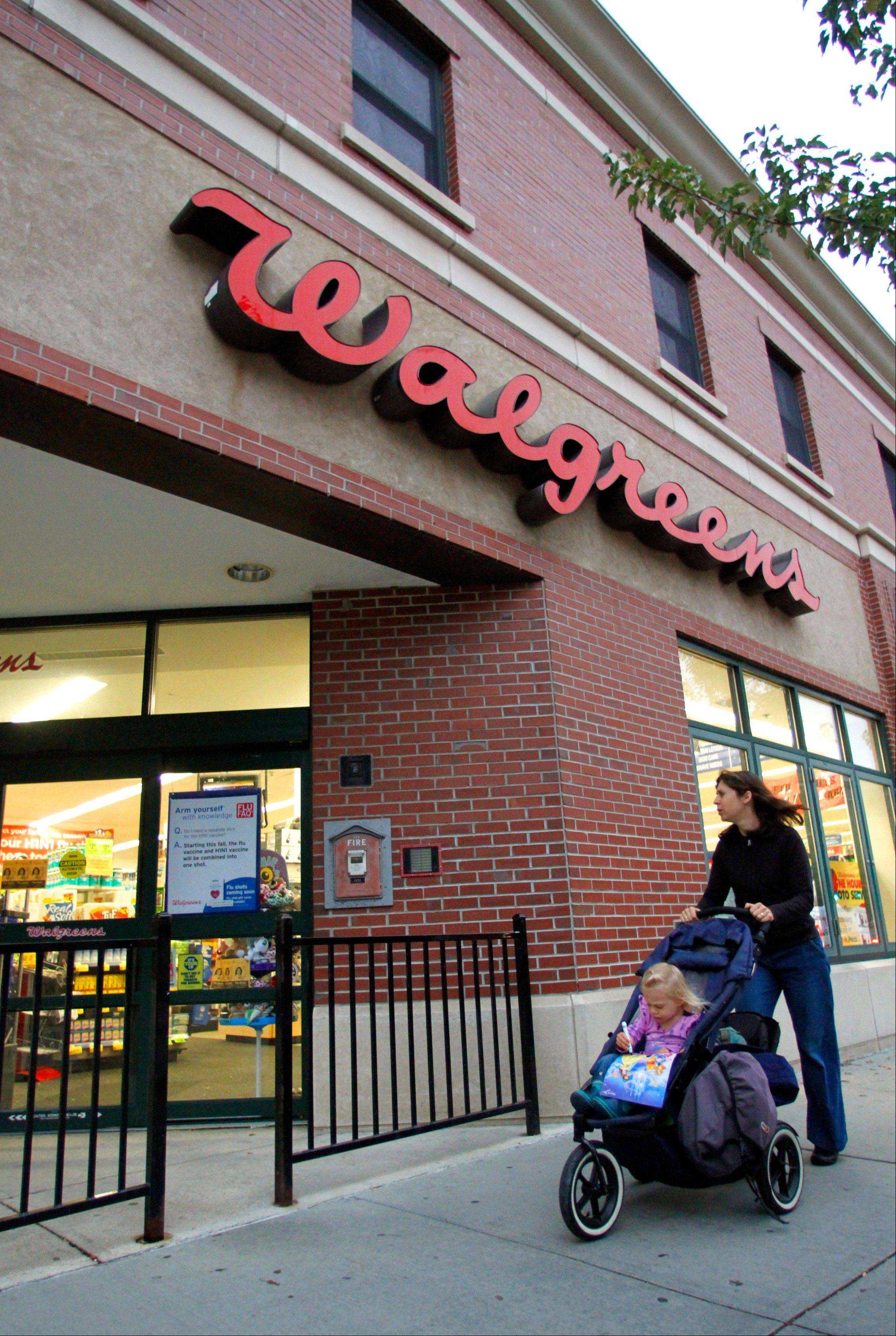 A passer-by pushes a baby carriage past the entrance of a Walgreens pharmacy.