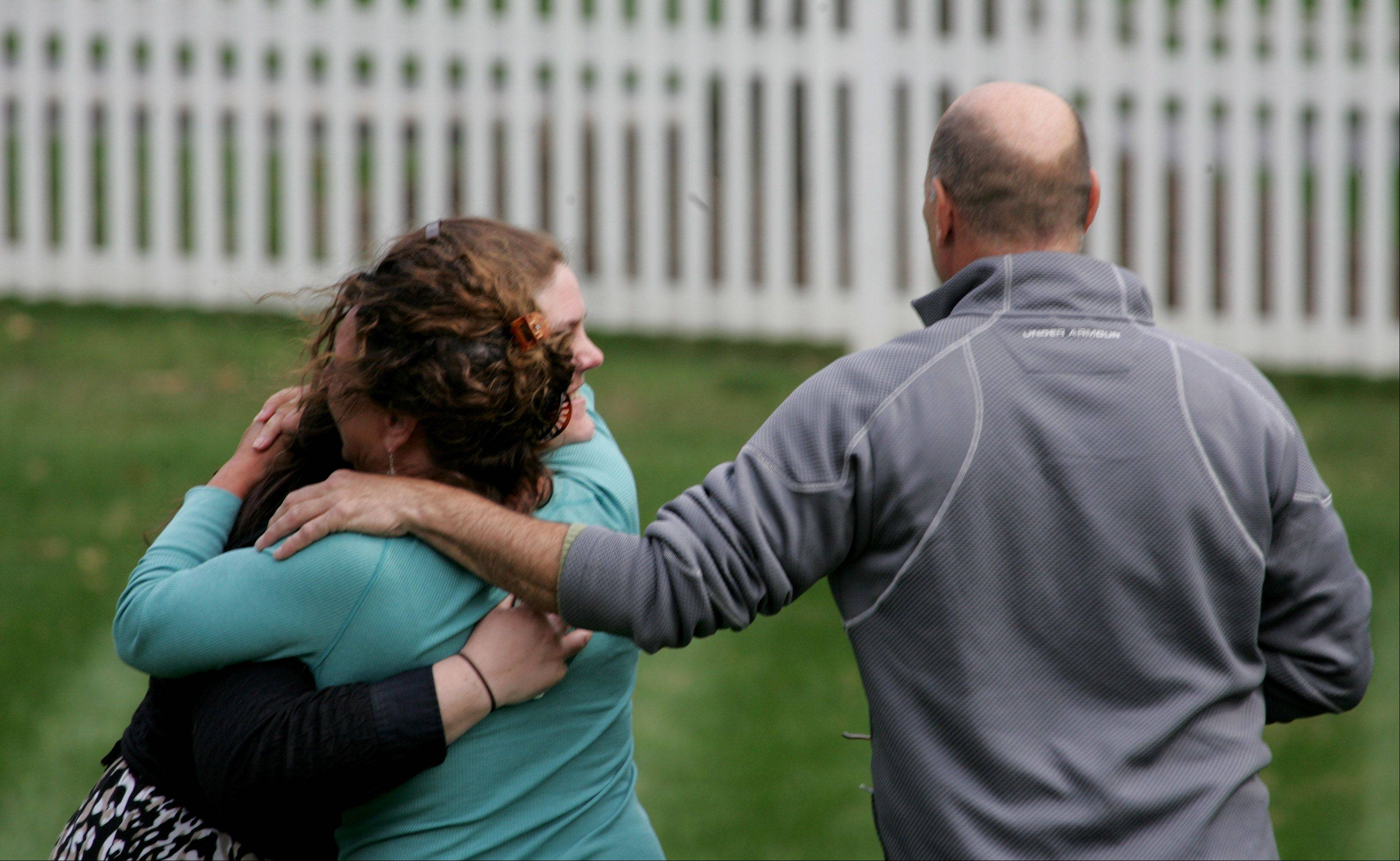 The owners of a house on the 1S400 block of Sunnybrook Lane near Glen Ellyn get a hug during a fire on Tuesday.