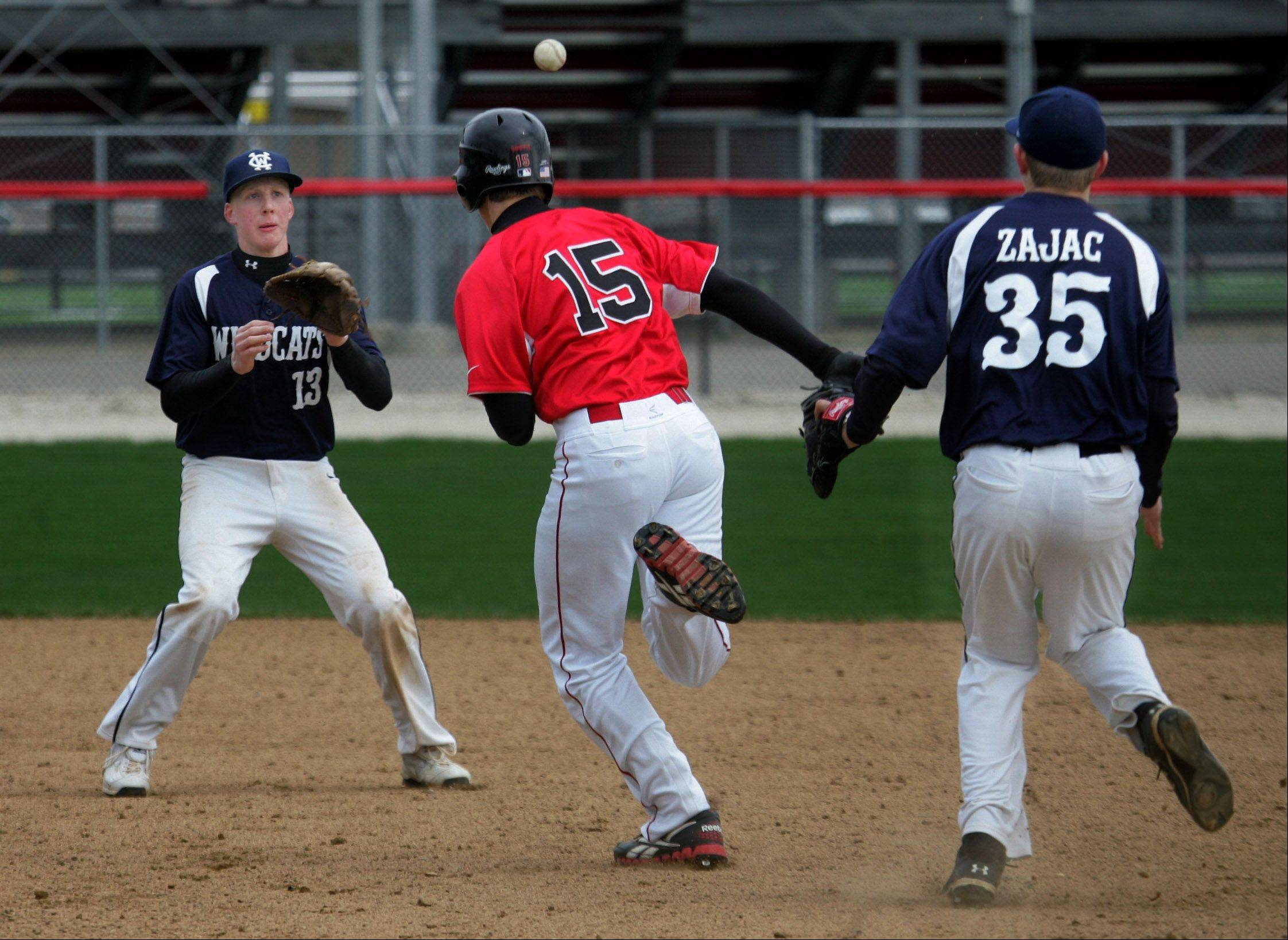 Grant baserunner Simeon Lucas is caught in a rundown between first and second base as West Chicago's Ryan Koester catches the ball from Mike Zajac on Tuesday at Grant.