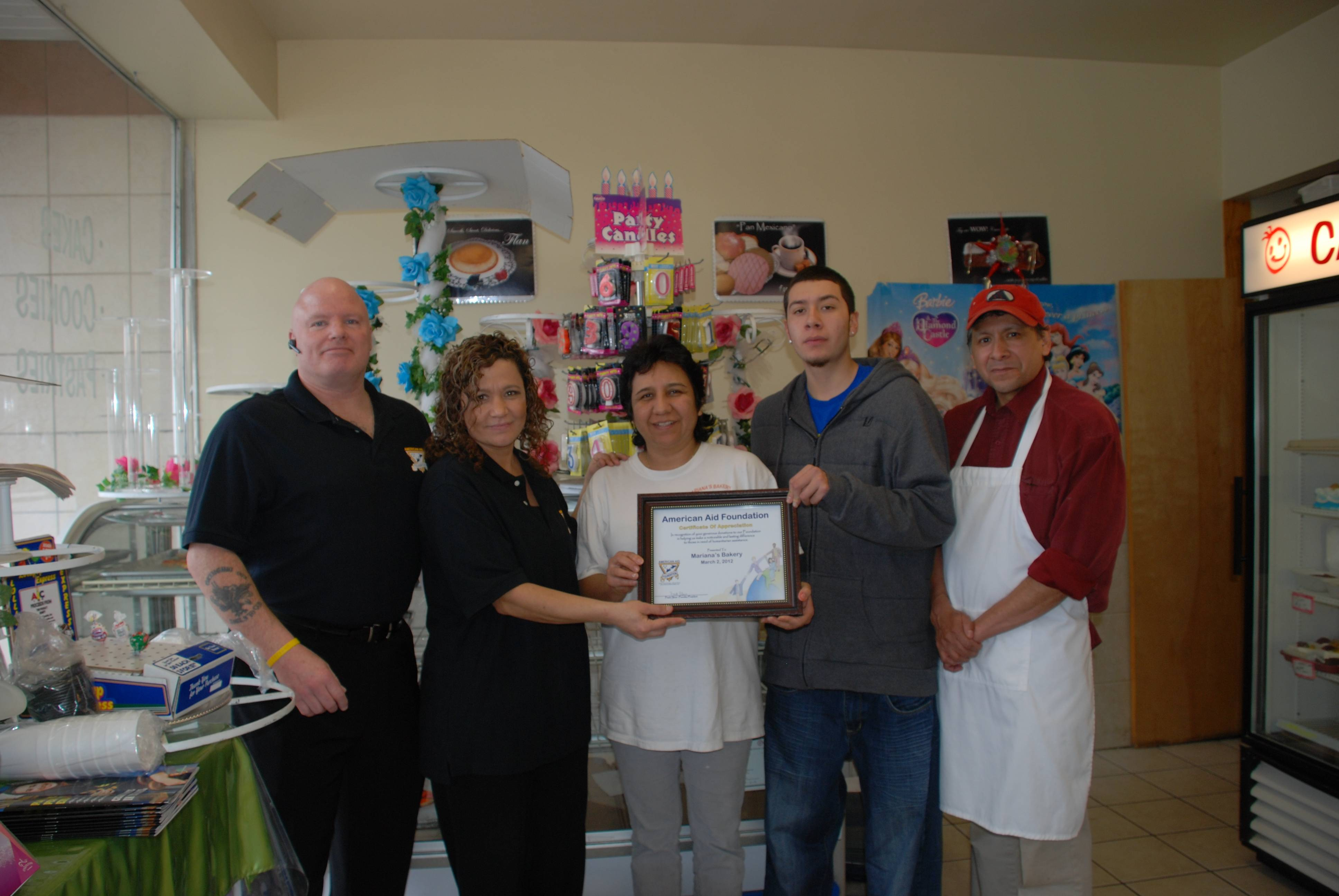 American Aid Foundation Founder/President Frank Slove & Director Carmen Gonzalez present Mariana's Bakery Owners Carmen, Miguel Jr.(son) and Miguel Sr. Gonzalez a Certificate of Appreciation for their continued generosity to the Foundation's programs. (L-R)