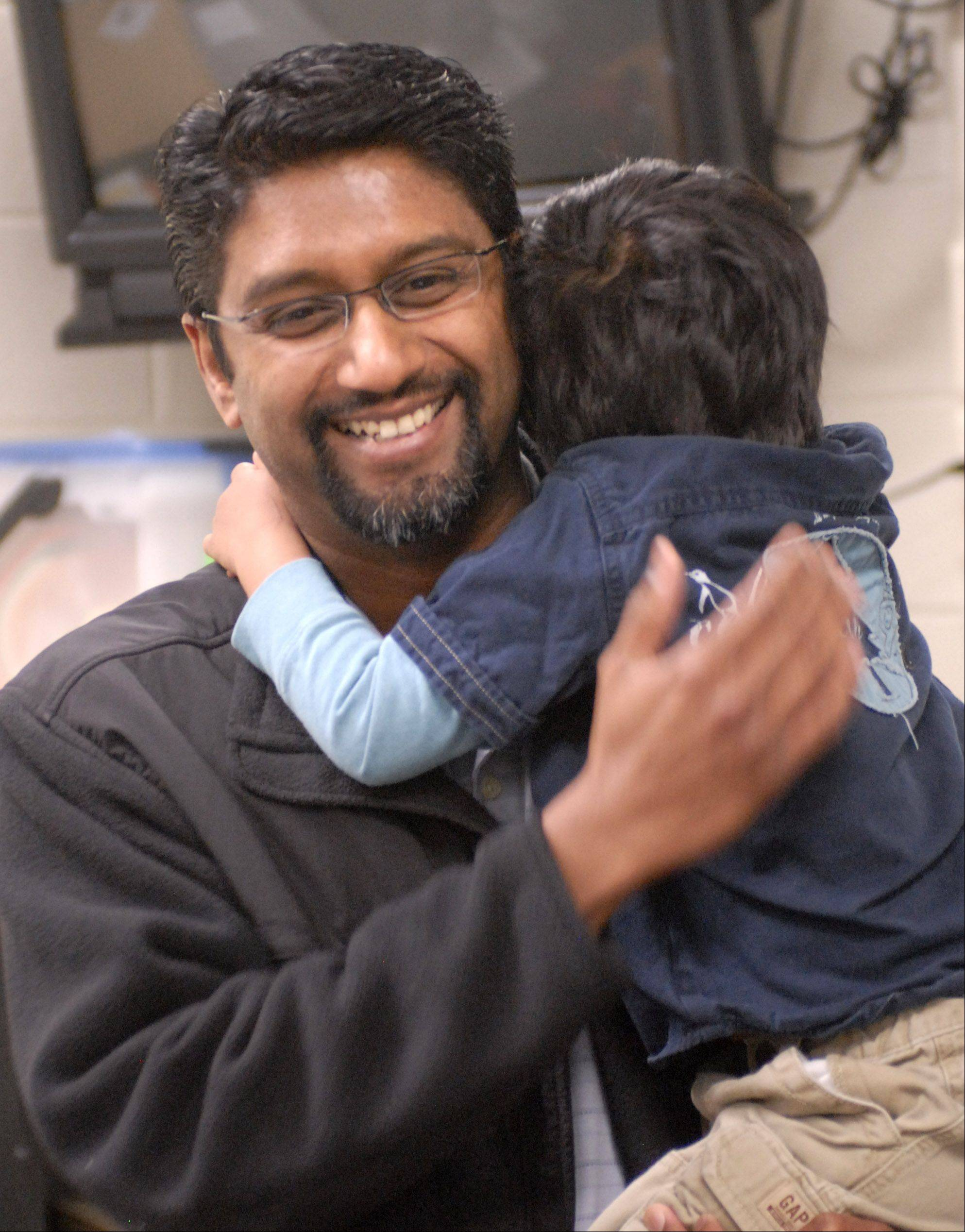 Stevenson High School math teacher Darshan Jain is all smiles while holding his 3-year-old son Eden after being presented with the Golden Apple Award in 2010.
