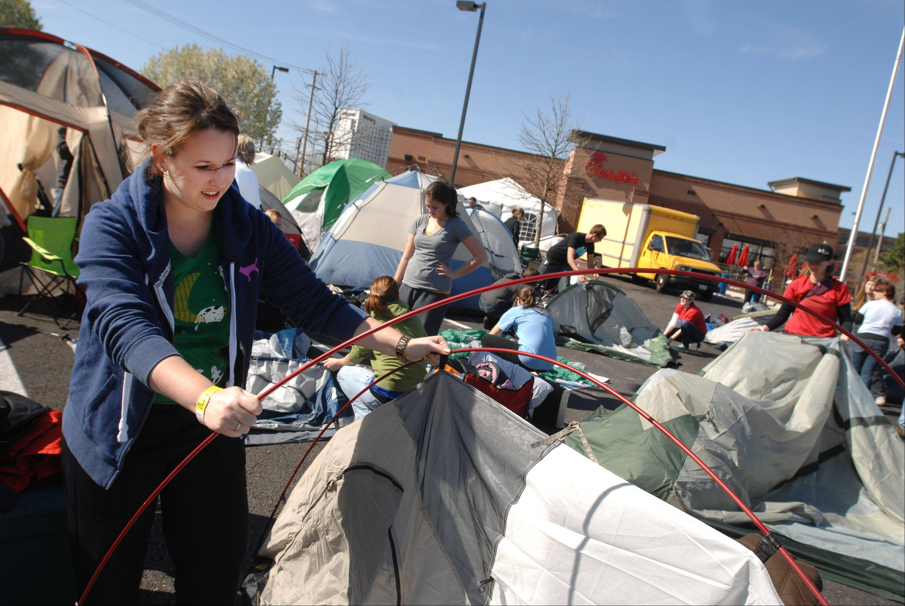 "Laura De Masie of Yorkville puts up her tent as she prepares for Chick-fil-A's grand opening today in Lombard. She and more than 100 others planned to camp at the restaurant for 24 hours in hopes of being among the ""First 100"" to snag 52 free meal certificates."