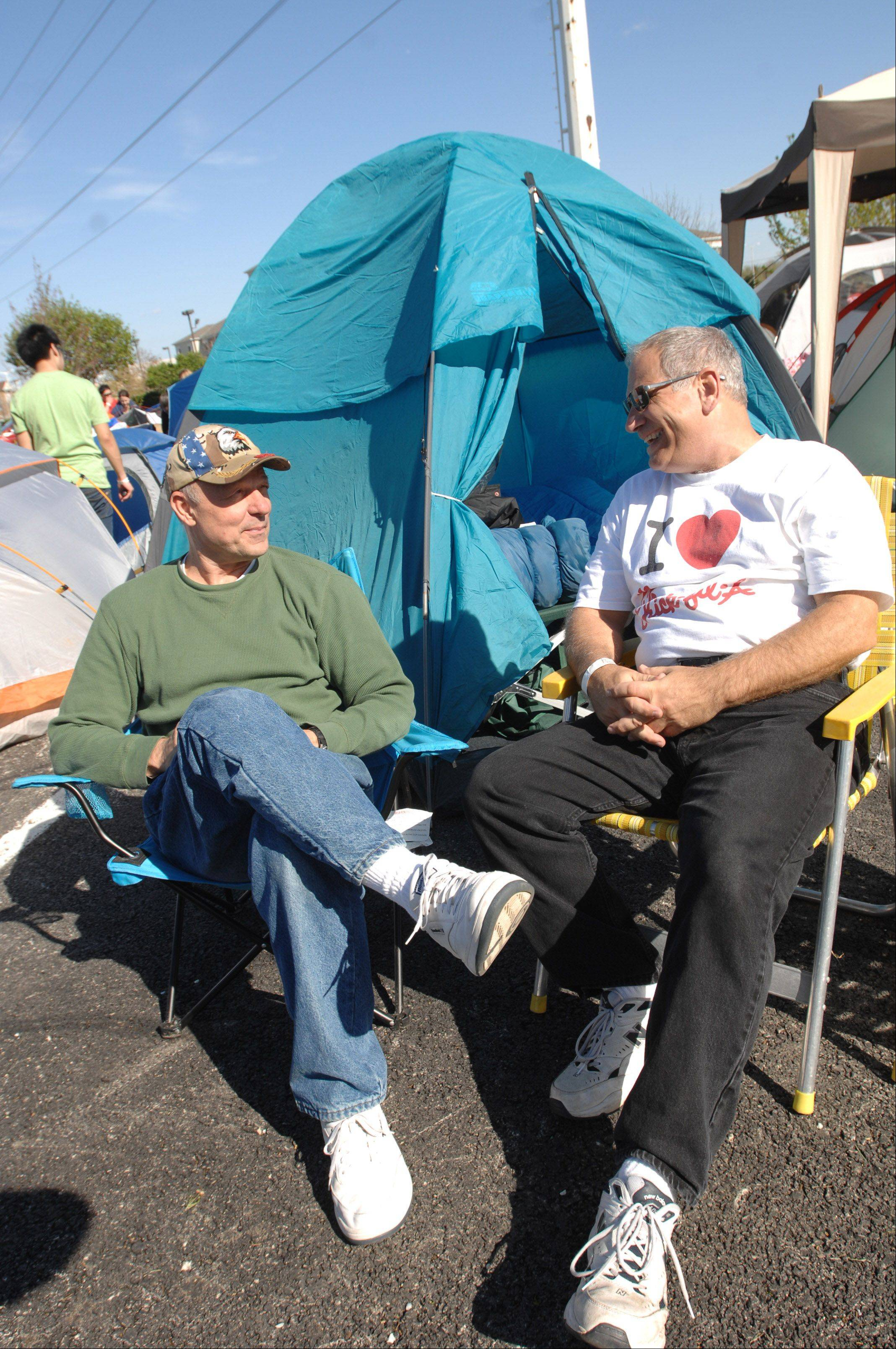 "Dan Dudek and Rich Fitzgerald chat in front of their tent Wednesday in Lombard while waiting for the area's sixth Chick-fil-A to open at 6:30 a.m. today. The restaurant hosted a 24-hour tailgate for fans trying to be among the store's ""First 100"" and win 52 free meal certificates."