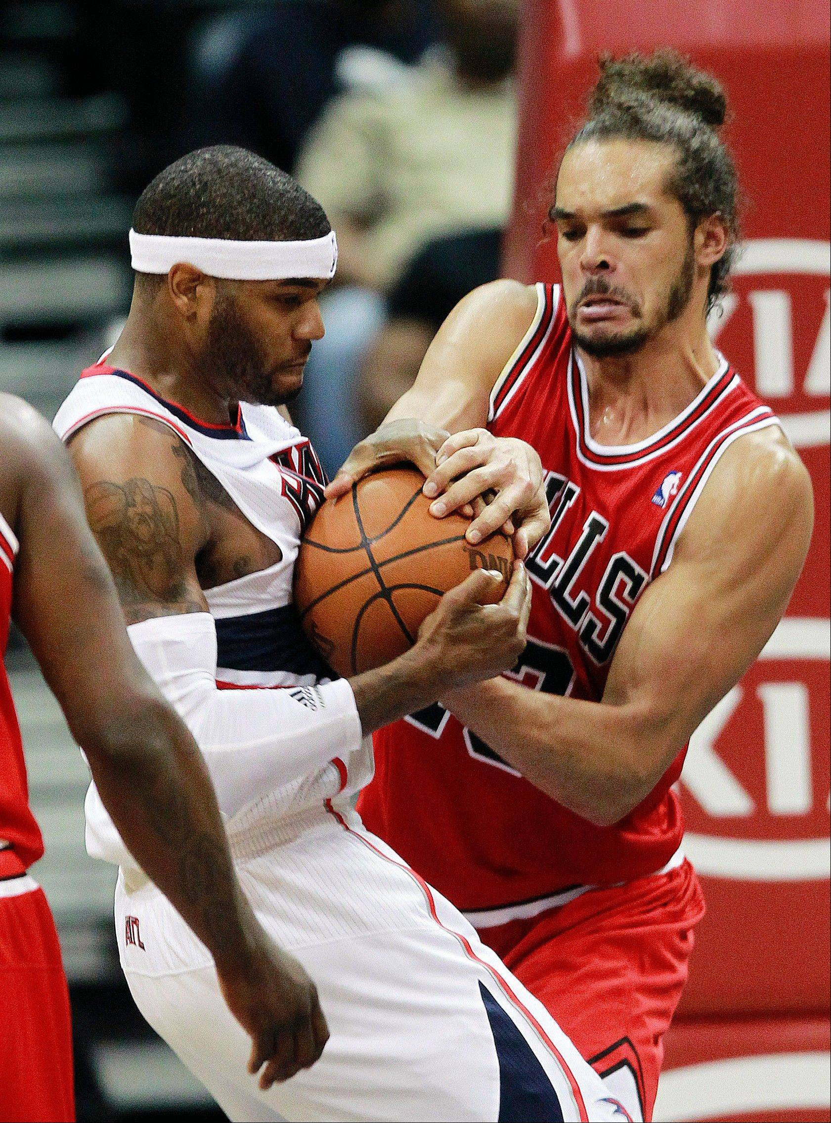 Bull center Joakim Noah struggles with Hawks forward Josh Smith for control of the ball Wednesday night.