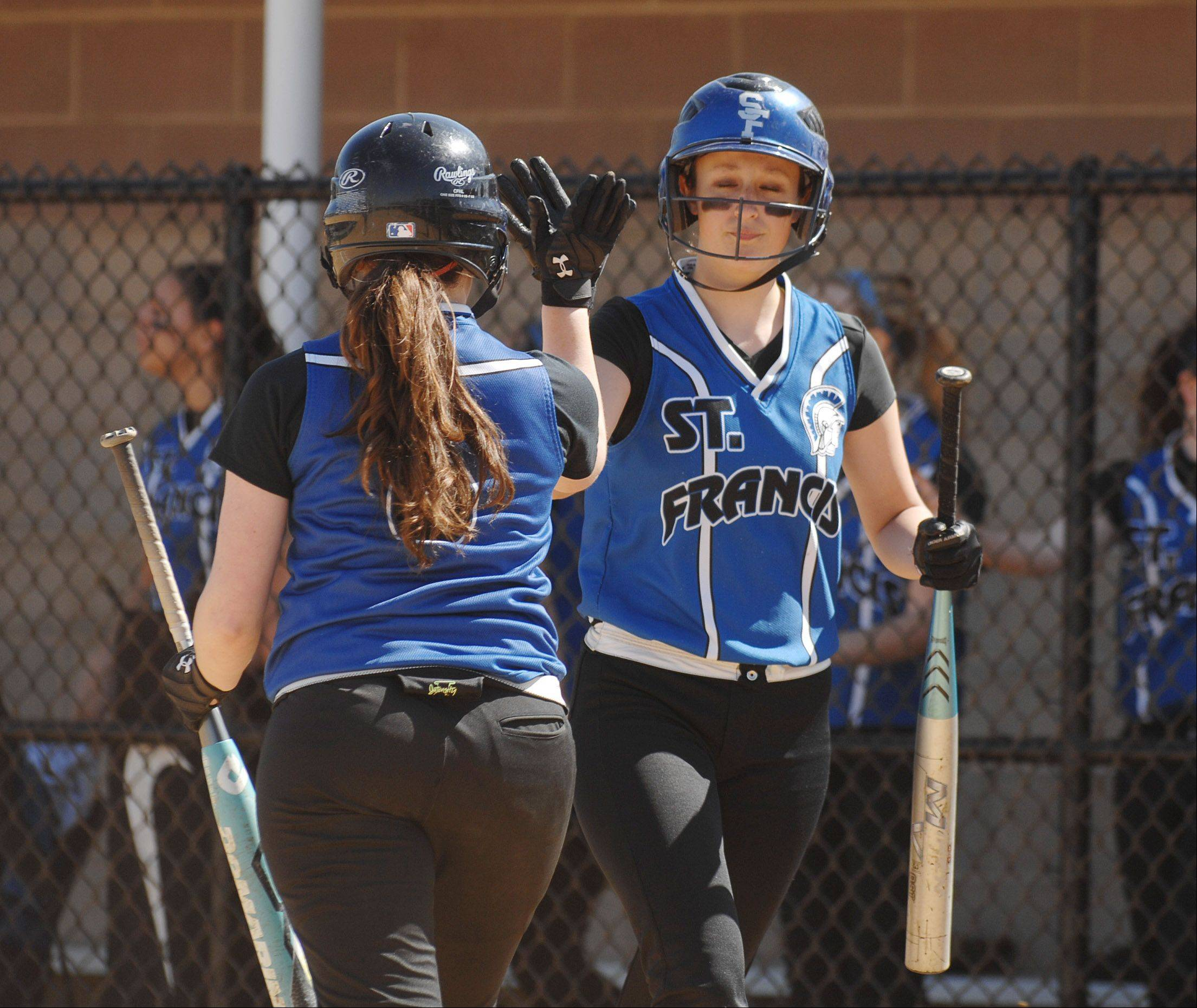 Blaine Carragher of St. Francis,left, and Maggie Remus do a high five after Carragher scored during the St. Francis at Addison Trail softball game Wednesday.