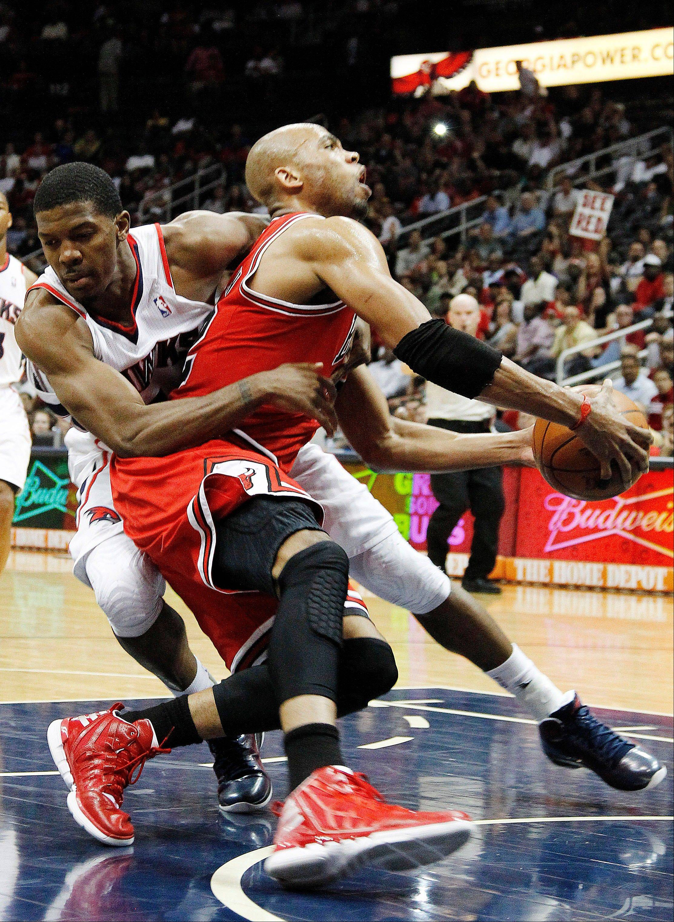 Bulls forward Taj Gibson is fouled by Atlanta Hawks shooting guard Joe Johnson ss he drives to the basket Wednesday in the second half.