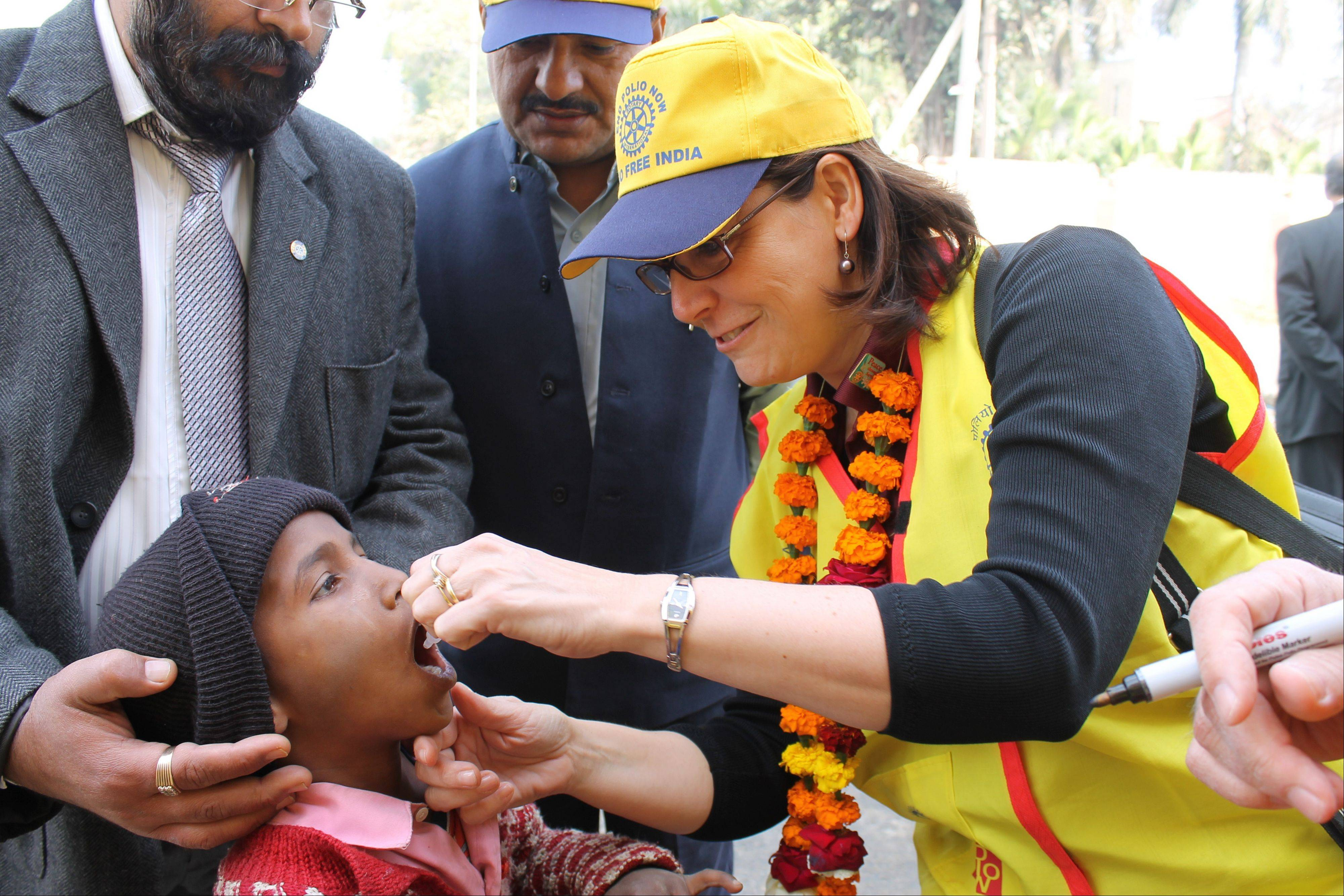 Nicki Scott, former president of the Rotary Club of Naperville Sunrise, administers the polio vaccine to a child in Sonipat, India, northwest of New Delhi. Scott and a group of 37 Rotarians from the United States and Canada joined thousands of other volunteers in India Feb. 19-21 to help with National Immunization Days.