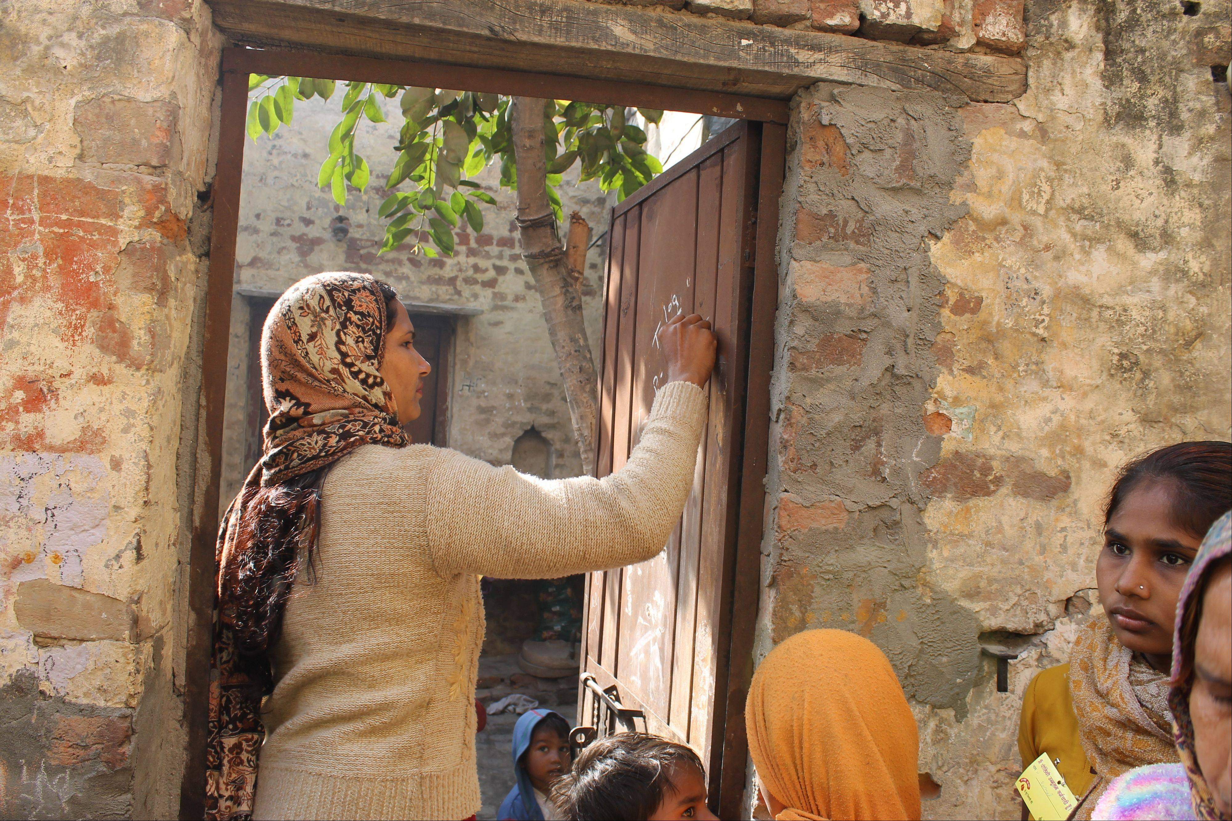 A worker marks a door with the number of children who are inside the home and the number of children who have received the vaccine. This door-to-door effort attempts to ensure that every child younger than 5 in India is inoculated during each National Immunization Days campaign.