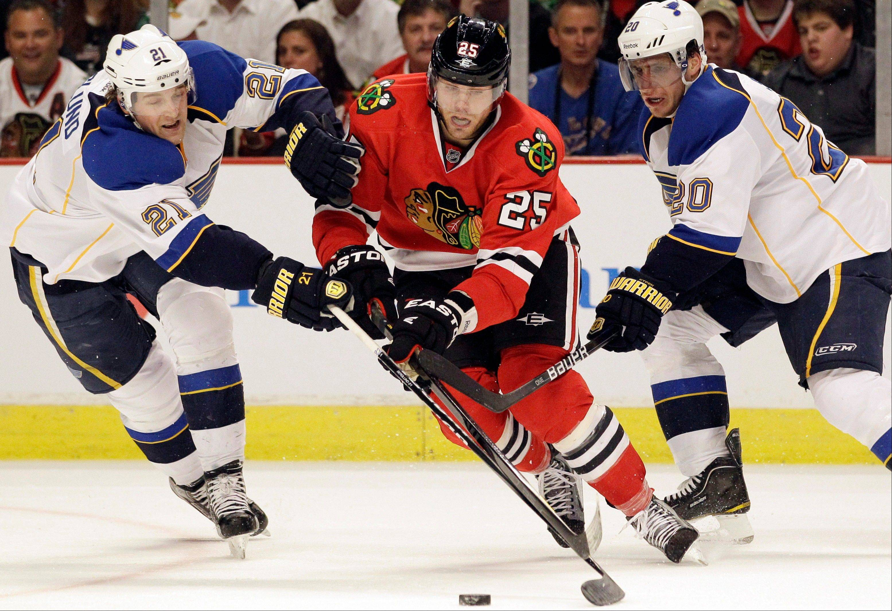 The Blackhawks' Viktor Stalberg works between St. Louis Blues' Patrik Berglund (21) and Alexander Steen (20) Thursday during the second period.