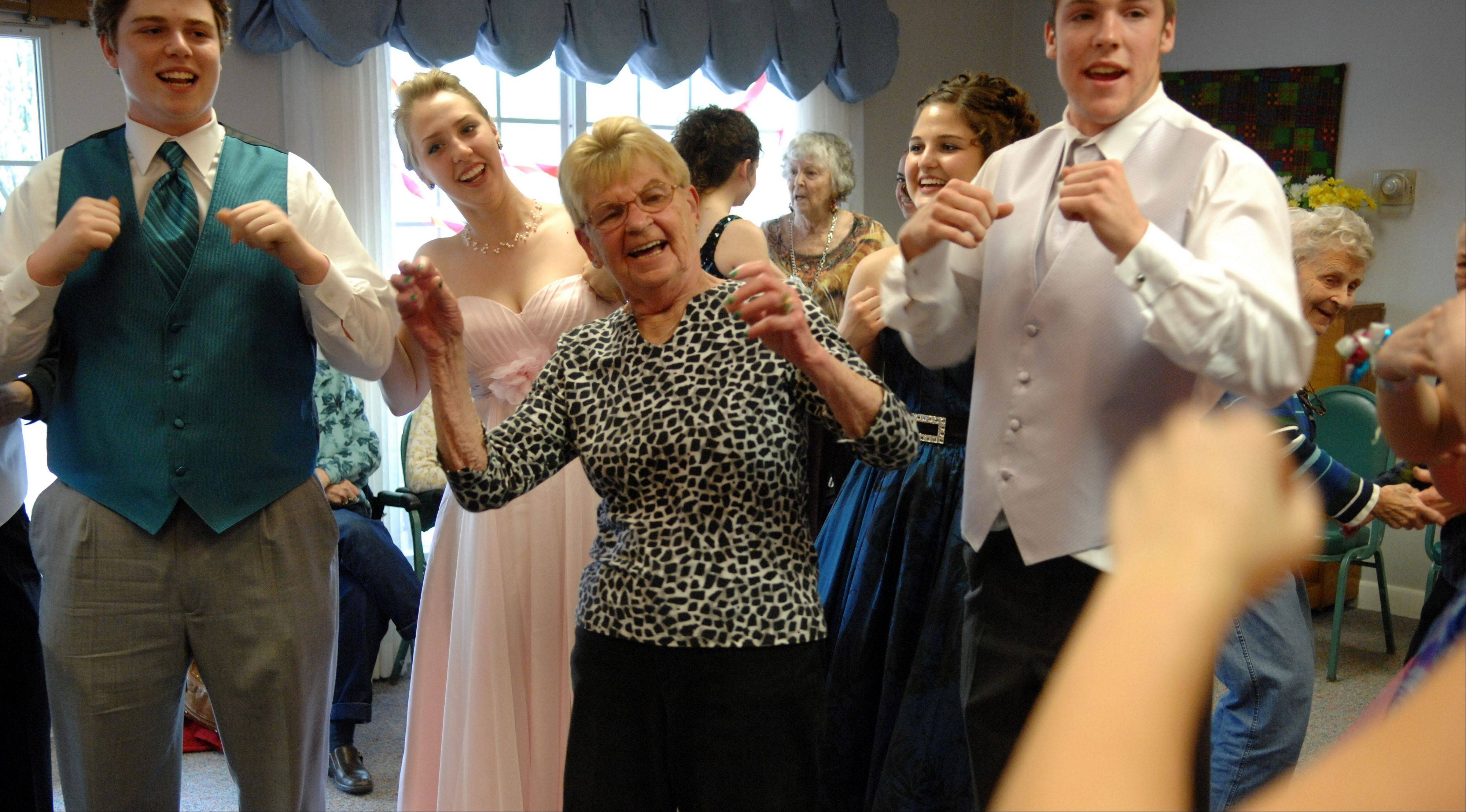 Arden Courts Memory Care resident Kathy Pandola does the chicken dance with Geneva High School seniors after a fashion show at the facility in Geneva.