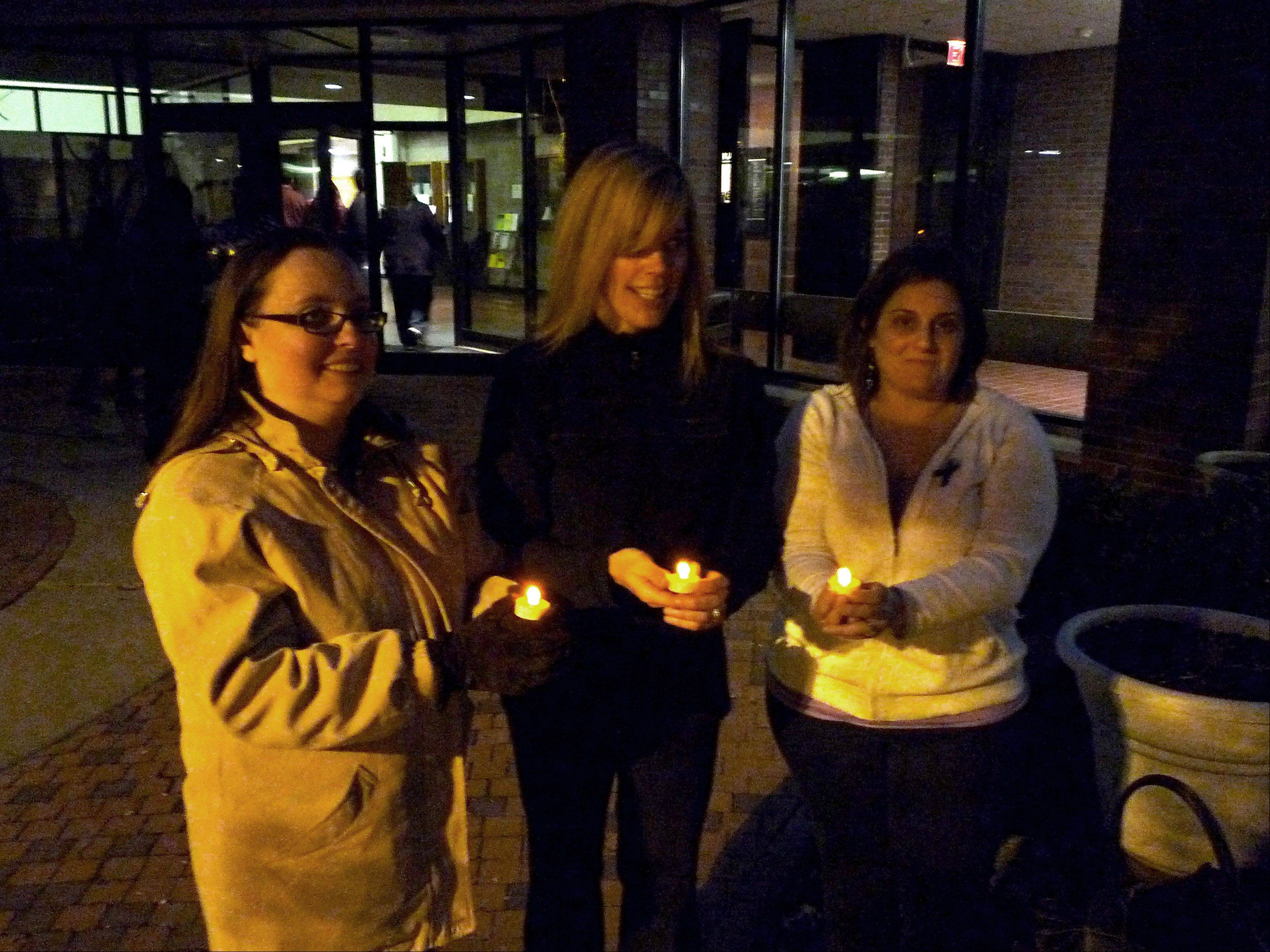 Participants in Oakton Community College's Take Back the Night rally on Friday hold candles in honor of victims of sexual abuse.