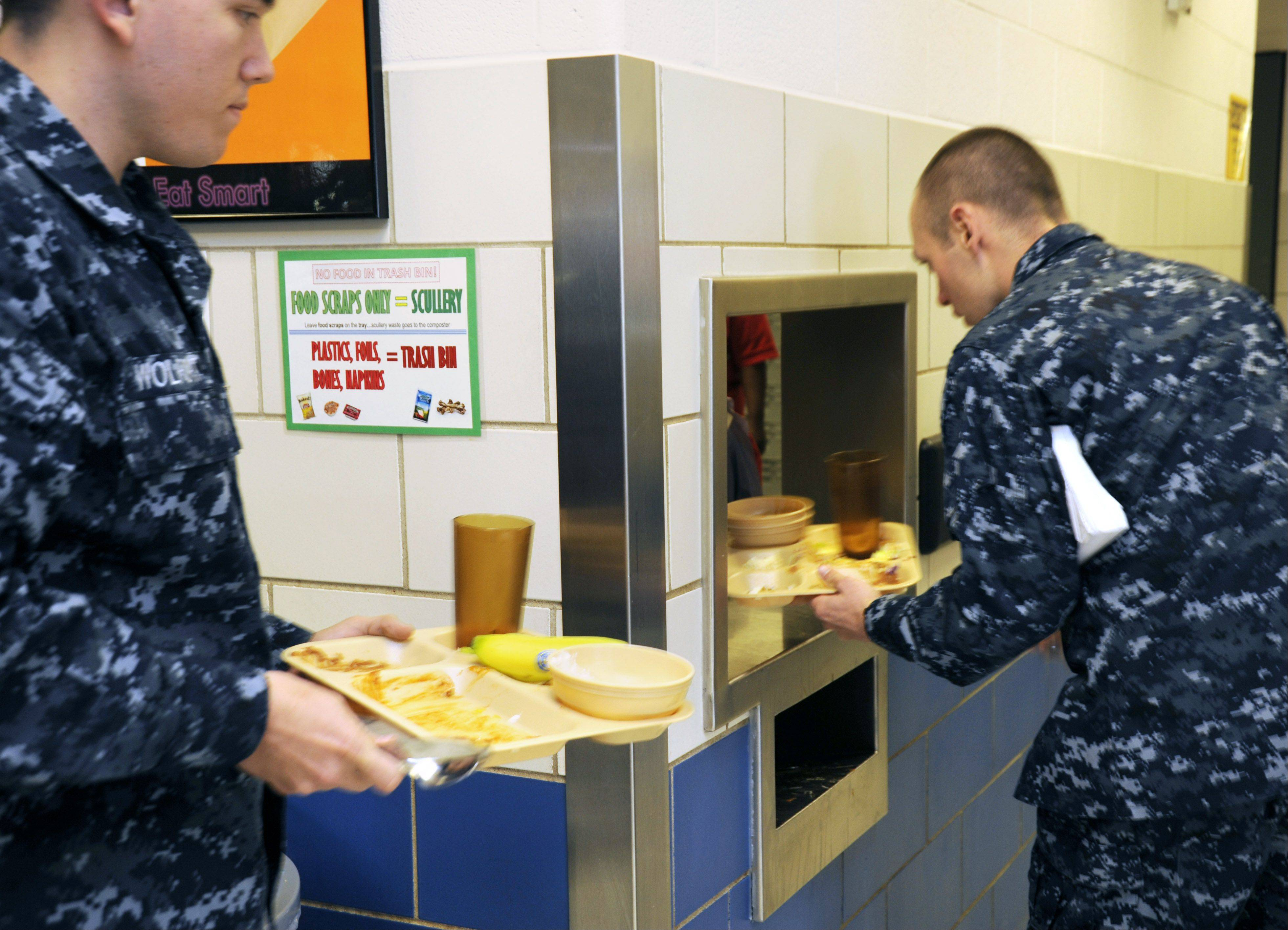 Signs posted in cafeterias at Recruit Training Command Great Lakes tell Navy recruits to separate trash from food waste before turning in their trays. Dishwashers spray the dishware clean, and leftover food flows to a composter unit outside the building.