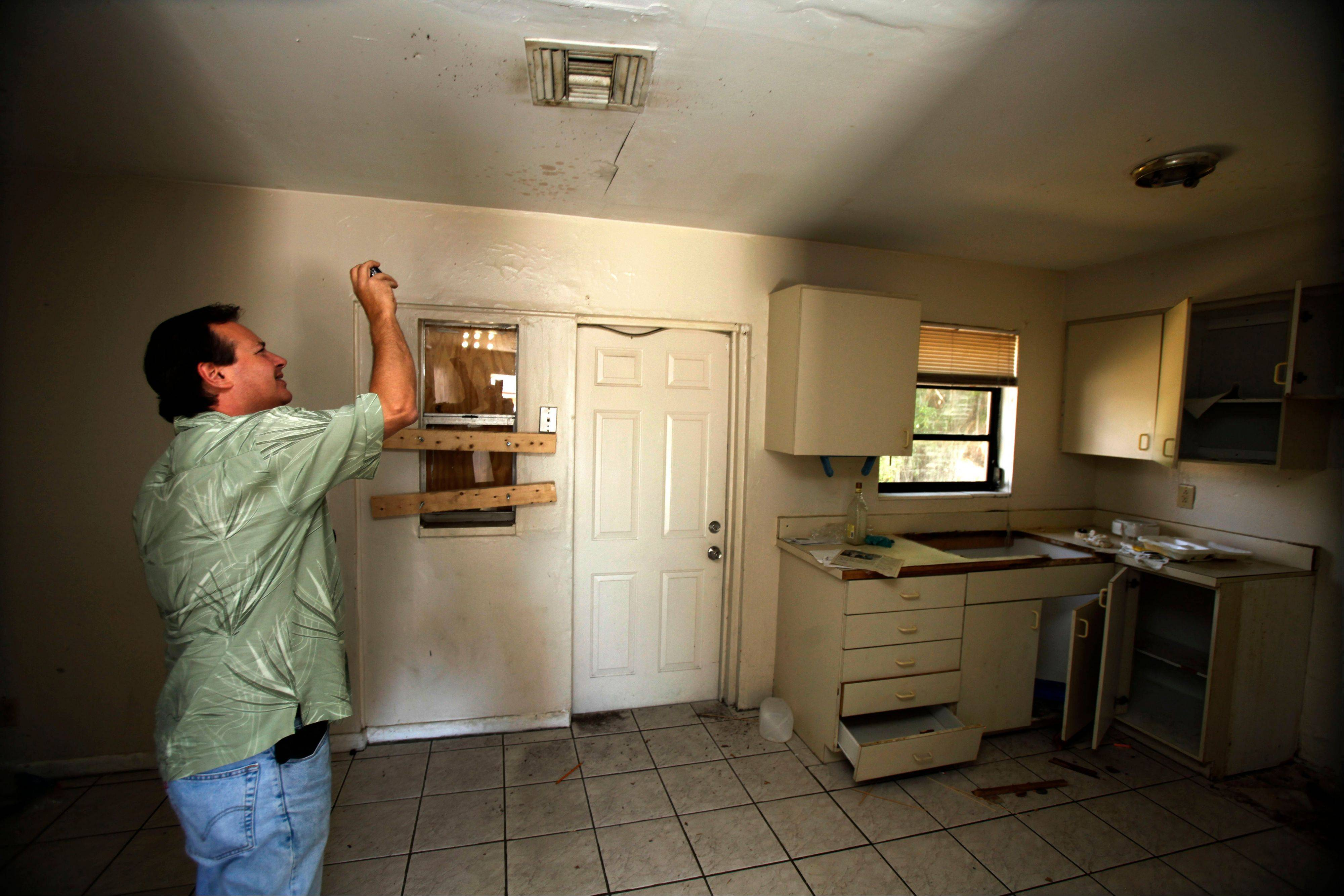 Frank Verna, a real estate agent who specializes in distressed properties, takes photos of a kitchen ceiling while checking a house in West Palm Beach, Fla. Thrashed by the mortgage and foreclosure disaster, Florida has thousands of distressed properties. But figuring out just how many is not so simple. Each month, analysts issue reports detailing the number of homes nationwide in foreclosure or held by banks. The implication is that if we can just find a cure for these loans and homes, either by matching buyers with houses or helping the borrowers stay put, the economy will at last be able to heal.