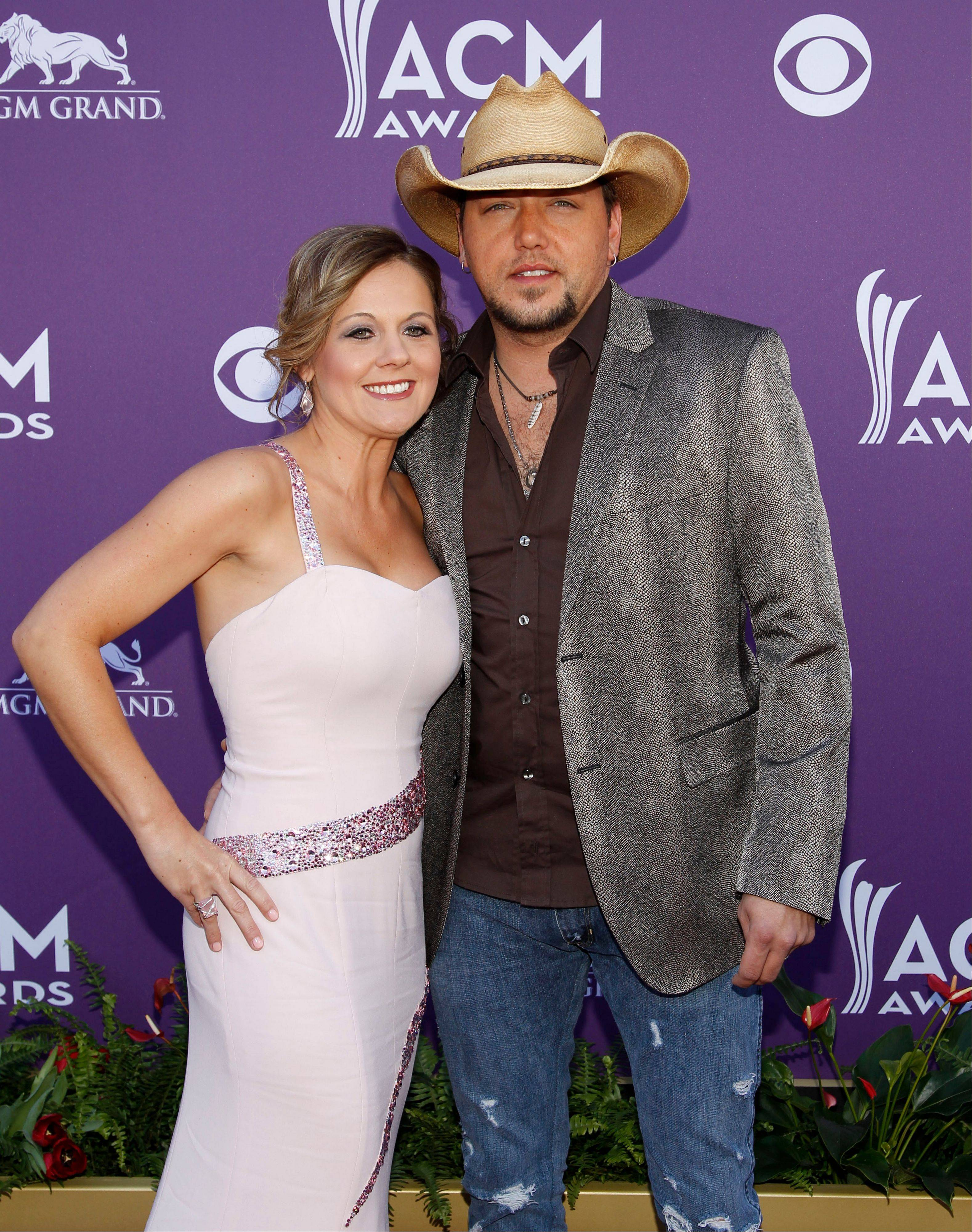 Jason Aldean, nominated for Male Vocalist of the Year as well as Enterainer of the Year escorts his wife, Jessica, into the awards show.