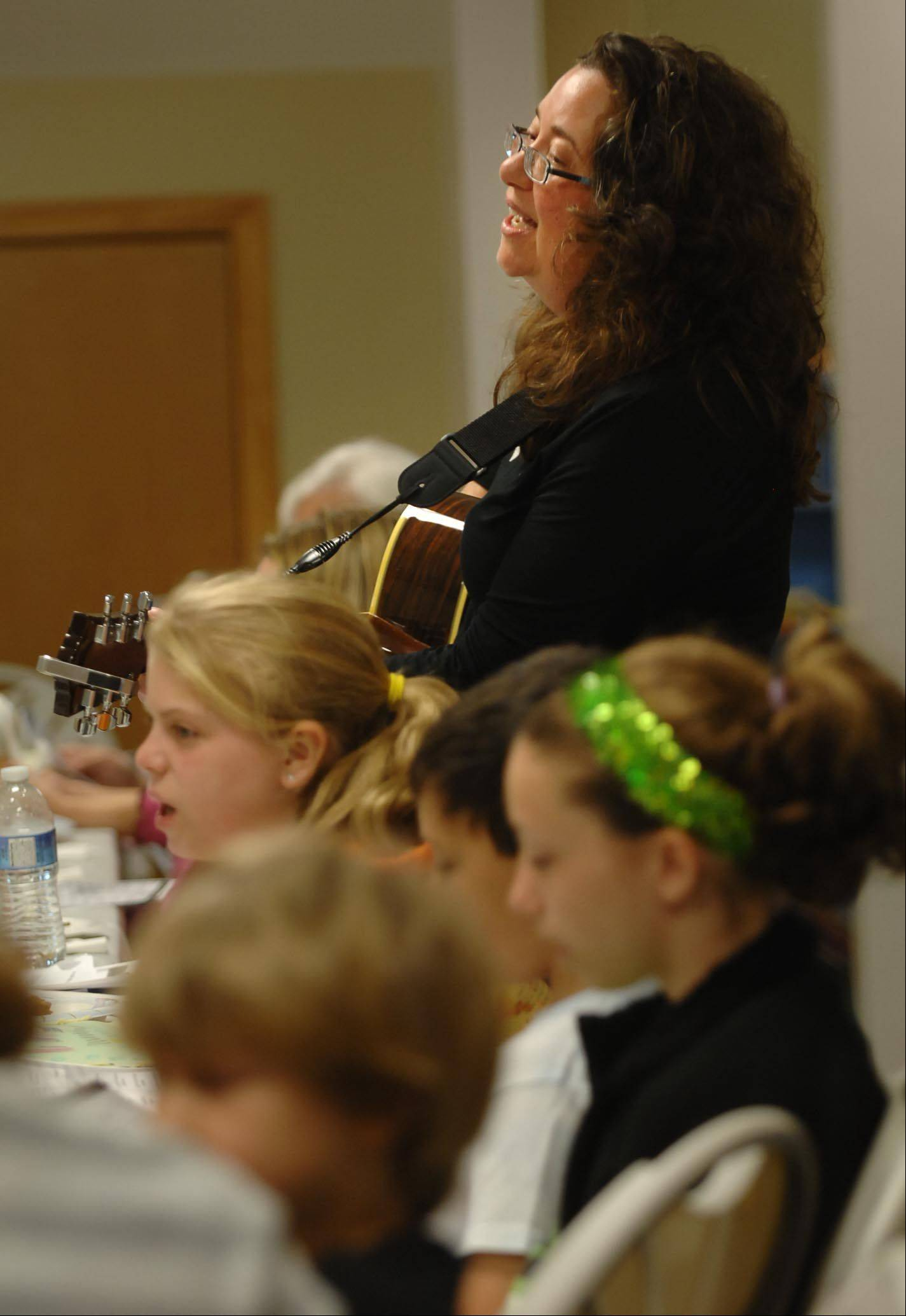 Rachel Yackley plays guitar and sings with the crowd as she leads a model Seder during religious school Sunday morning at the Fox Valley Jewish Neighbors in Geneva. Jewish families will participate in Seders during the first and second days of Passover April 6 and 7.
