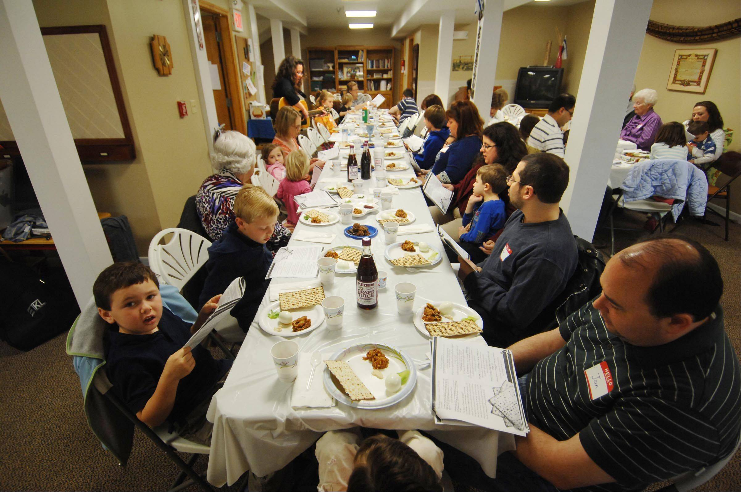 Families recite passages and sing as they attend a model Seder during religious school Sunday morning at the Fox Valley Jewish Neighbors in Geneva. A traditional Seder is meant to be participatory with all members of a family contributing to retelling the story of Passover.