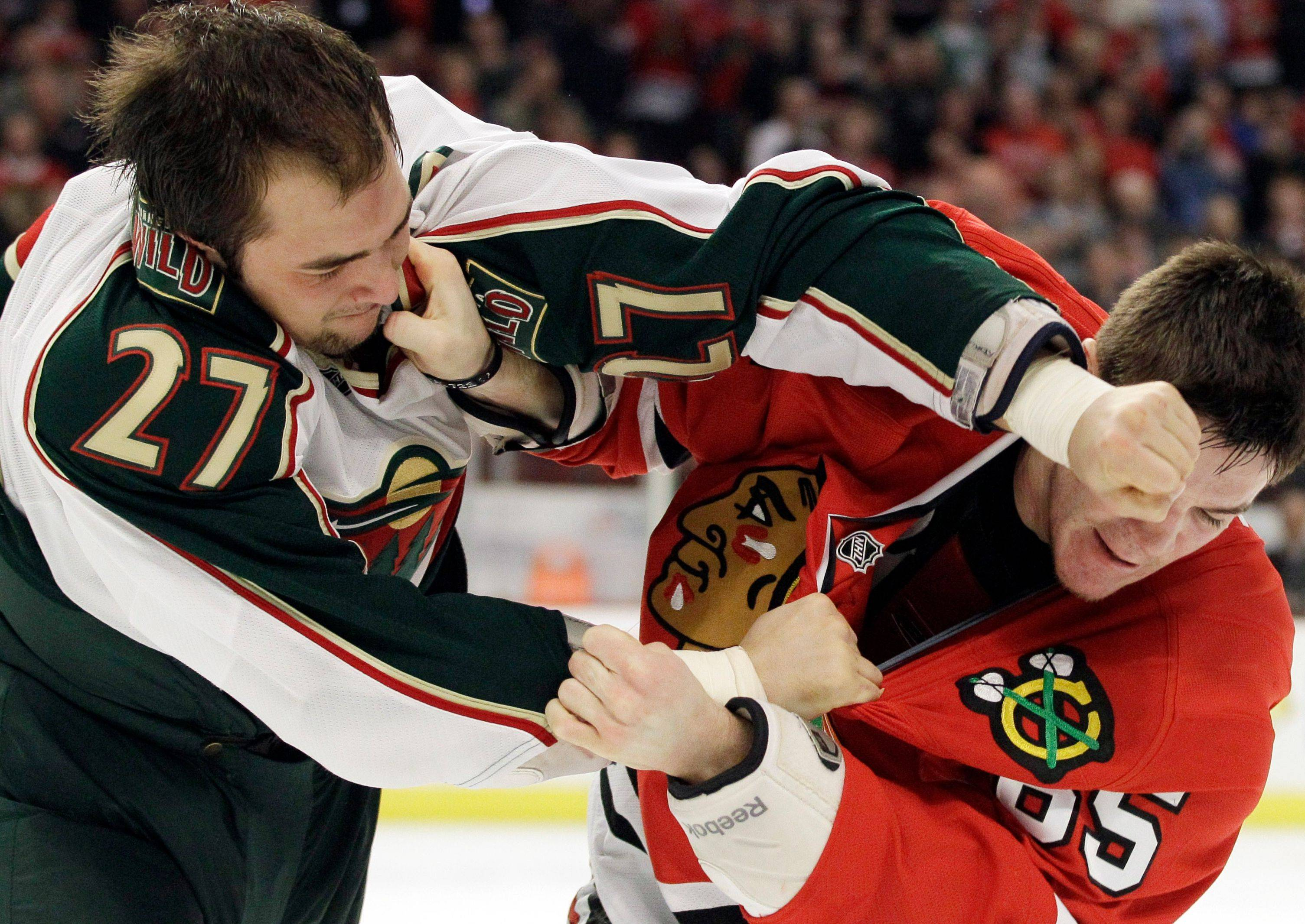 The Wild's Corey Almond, left, fights with the Blackhawks' Andrew Shaw during the second period Sunday night.