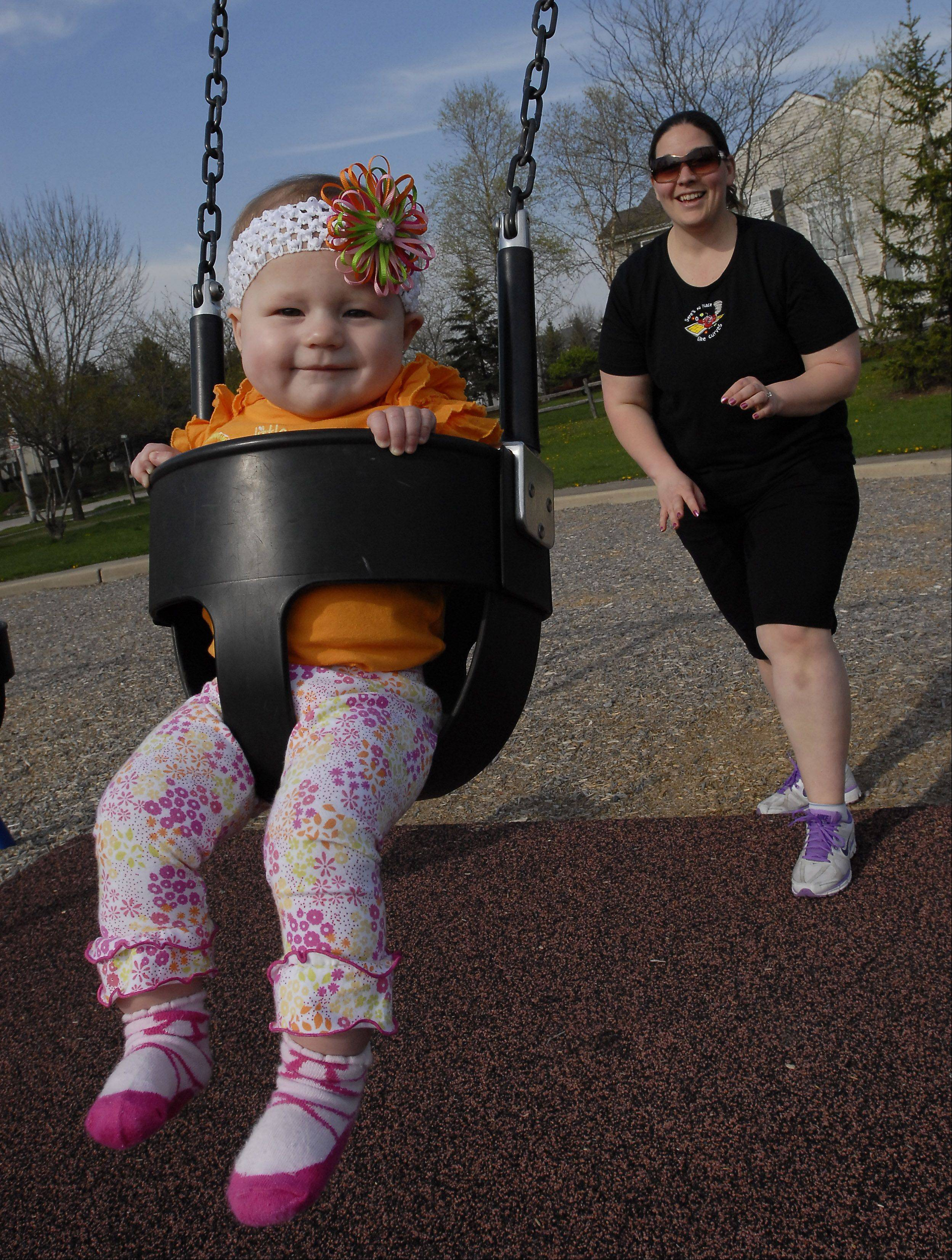Katie Przyszlak gets some exercise pushing her daughter, Addison, on the swings at a park near their home in Schaumburg.