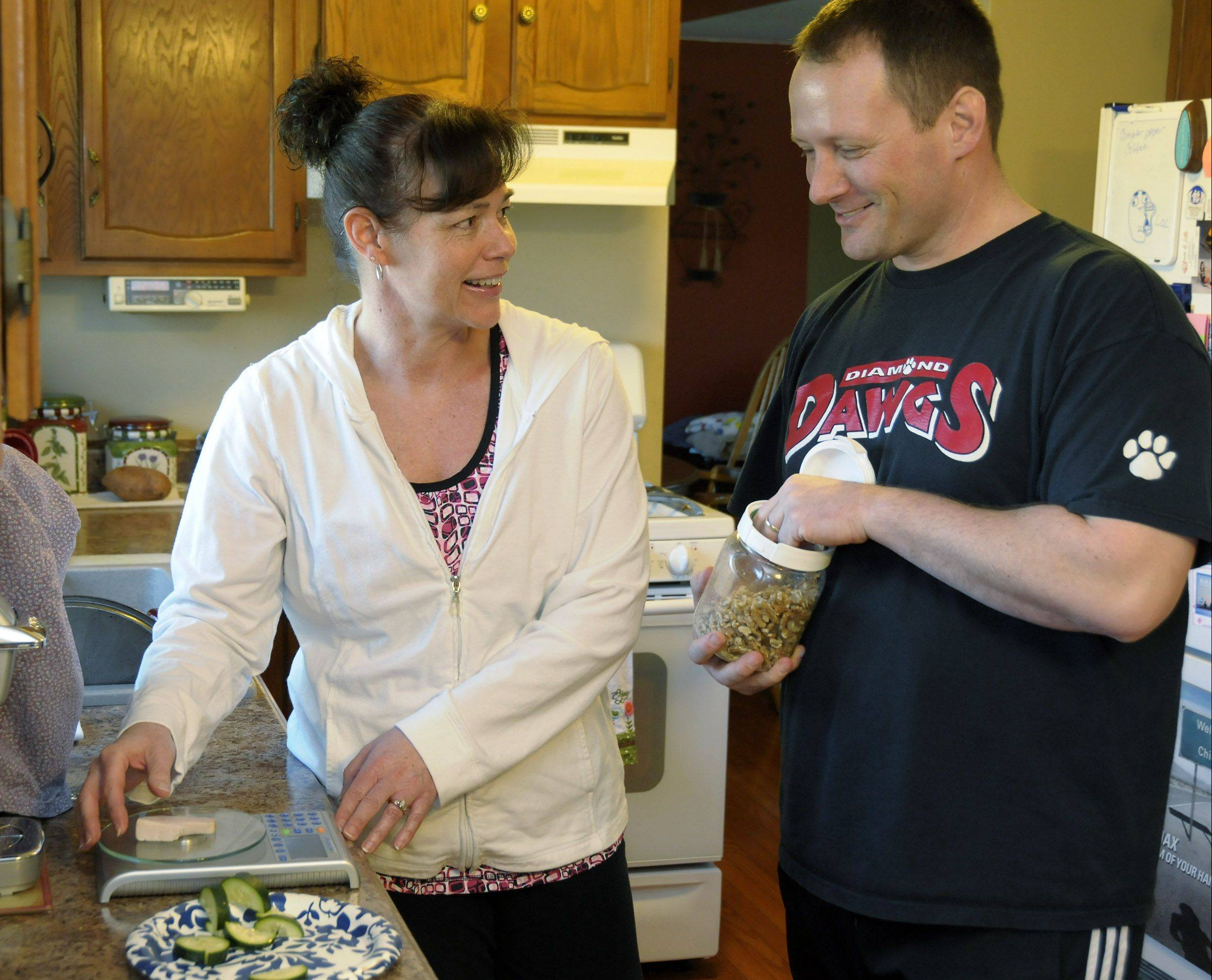 Brian Corrigan and his wife, Wendi, measure out one of his five small daily meals.
