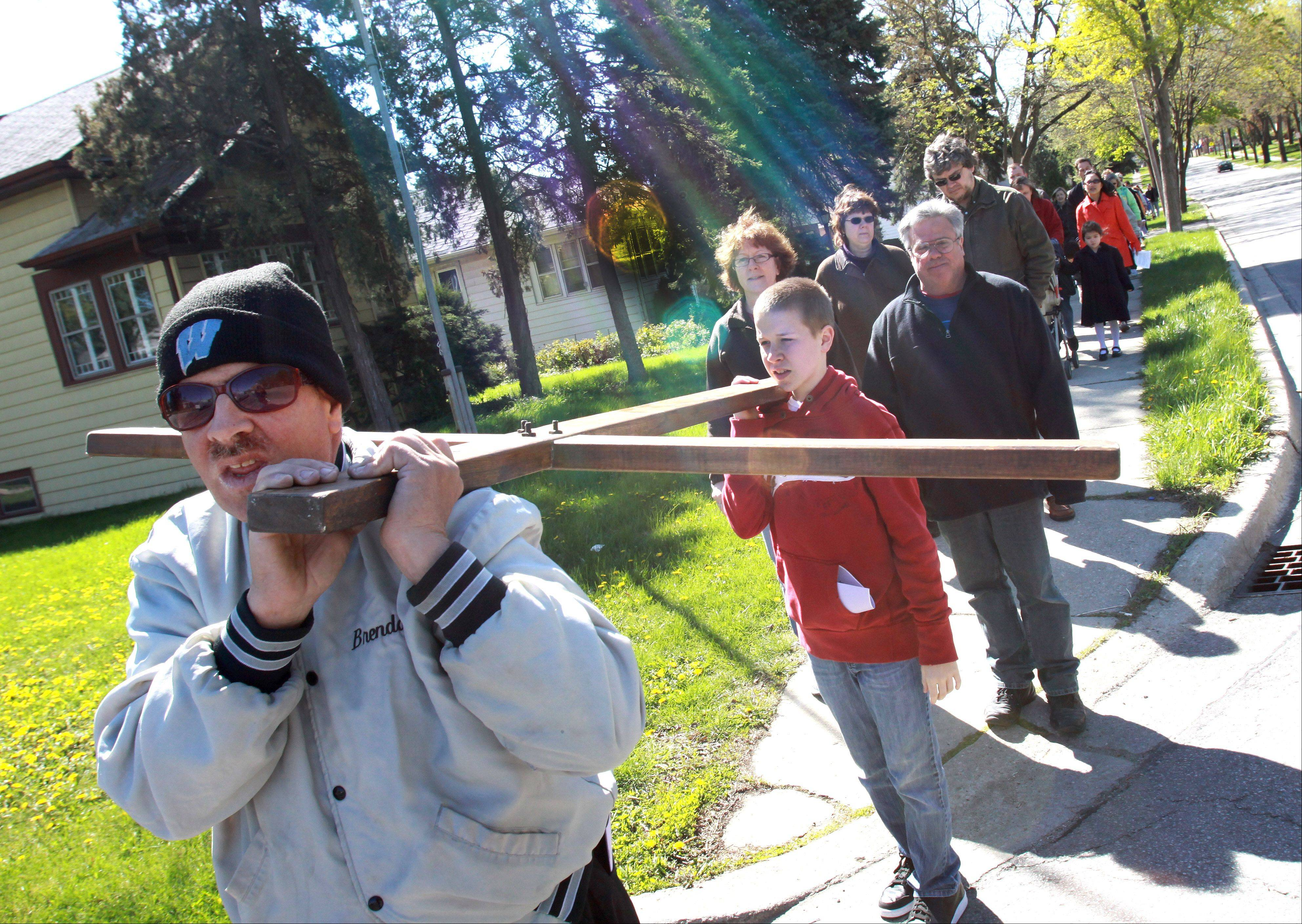 Brendan McArdle of Villa Park carries the cross with help from Ethan Wallace during St. Alexander Church's Good Friday Walk in Villa Park. This is the 20th year the church has held the walk.