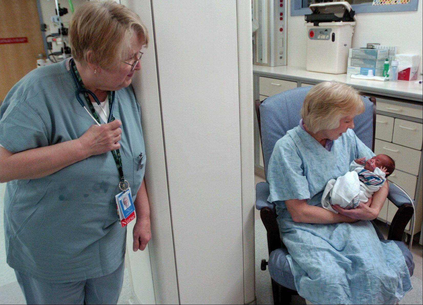Registered nurse Mary Jane Bennett peeks in on volunteer Trudy Lewis with a 3-month-old in the Neonatal Intensive Care Unit at Advocate Lutheran General Hospital.