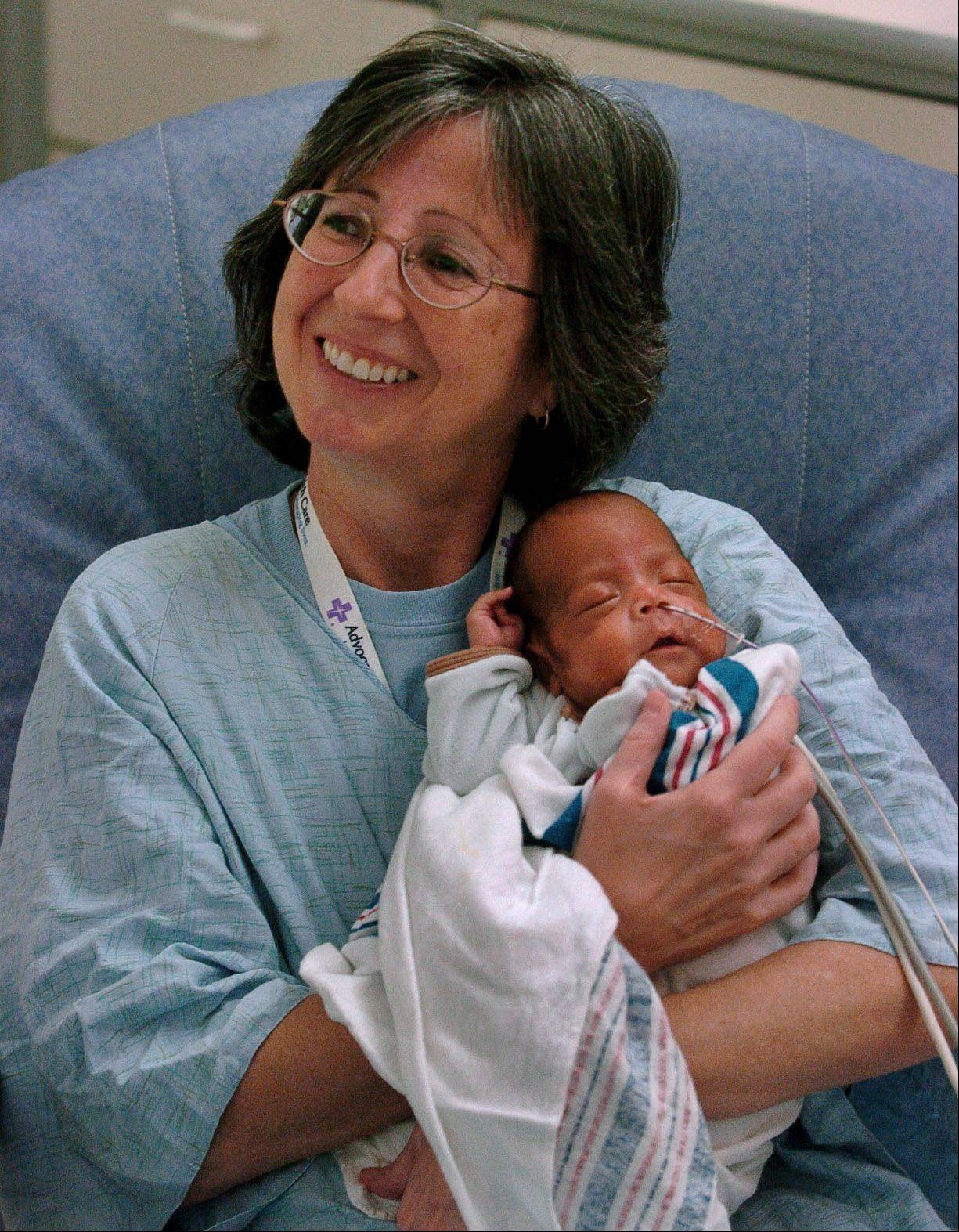 Volunteer Laura O'Shea holding a 3-month-old in the Neonatal Intensive Care Unit at Advocate Lutheran General Hospital in Park Ridge.