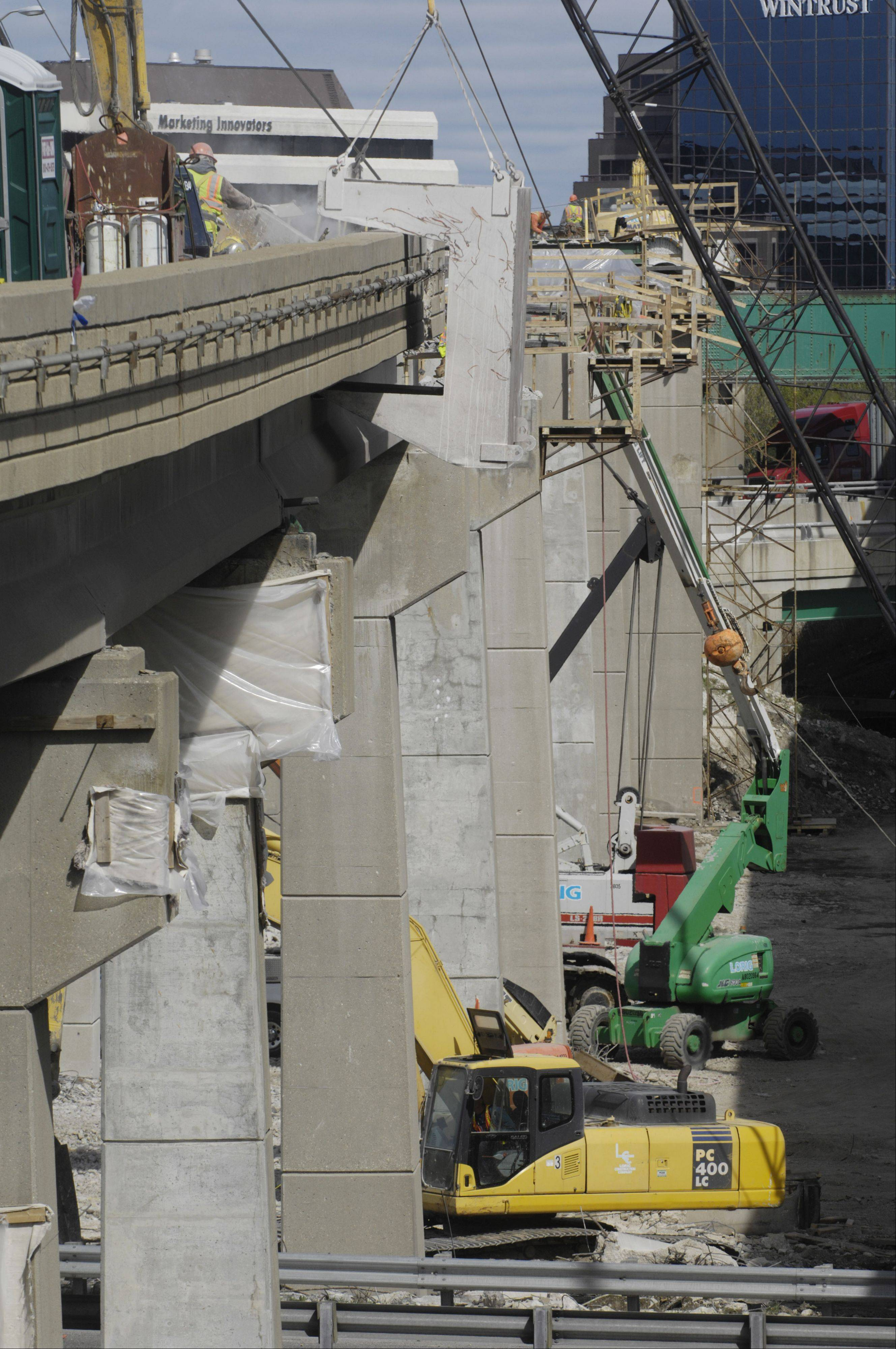 The deck of the existing tri-level bridge connecting northbound I-294 to westbound I-90 is being removed during reconstruction of the roadway.