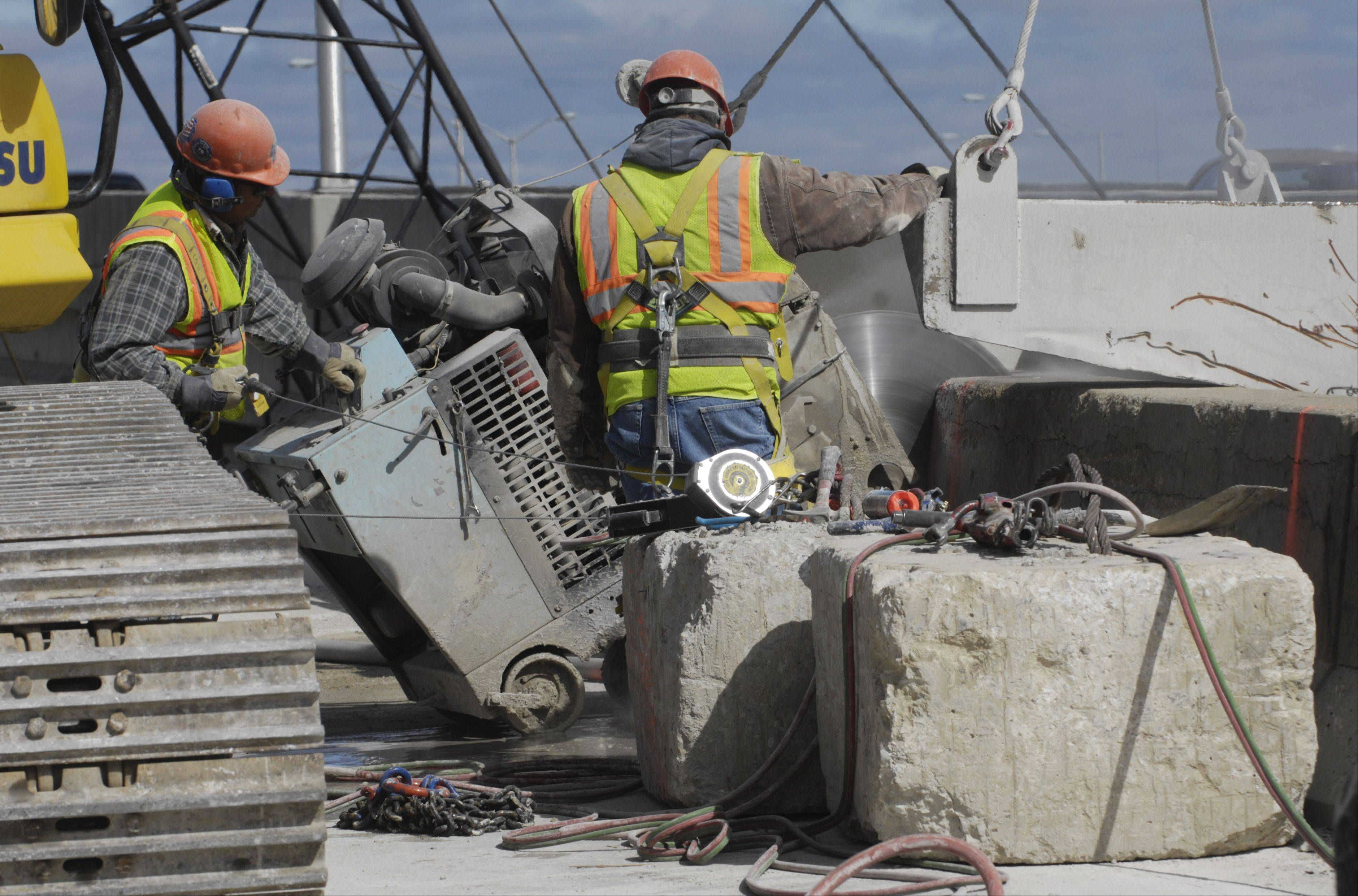 Construction workers saw through concrete during removal of the deck of the existing tri-level bridge connecting northbound I-294 to westbound I-90.