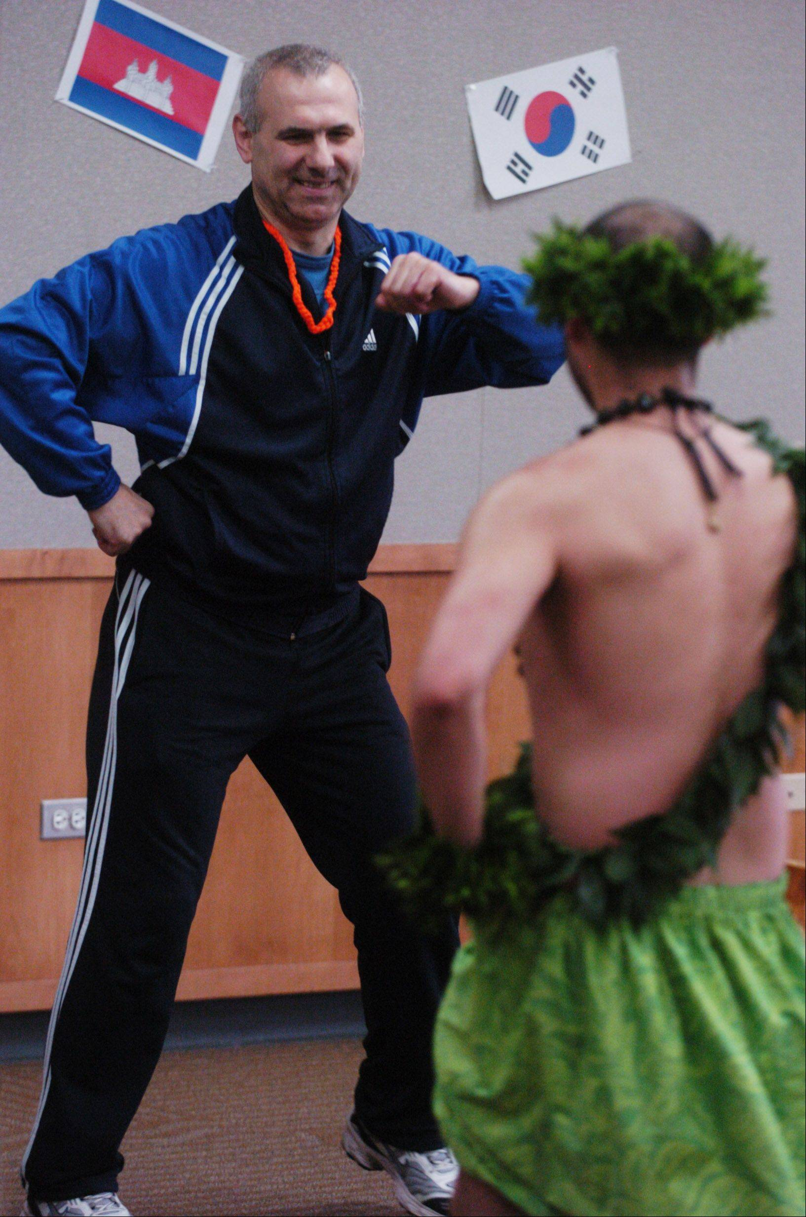Stoyan Kovatchev of Lake Zurich learns to hula as the Barefoot Hawaiin Dancers perform at the Ela Area Public Library in Lake Zurich Saturday.