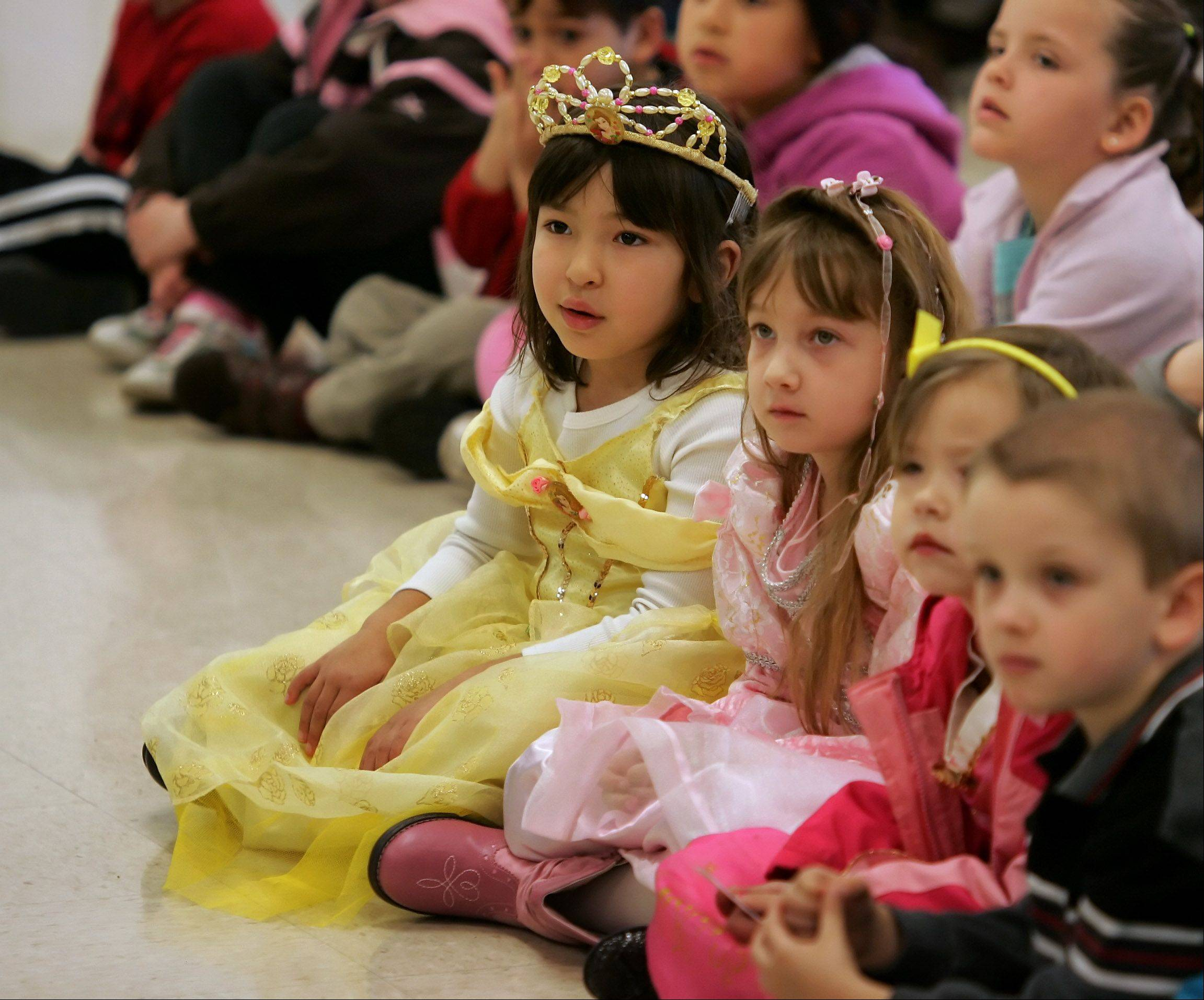 "Five-year-olds Leah Kim, left, and Morgan Jacobson, both of Mundelein, dress as princesses as they watch the production of ""The Tale of Beauty and the Beast"" Thursday by The Neighborhood Players at Robert W. Rolek Community Center in Round Lake."