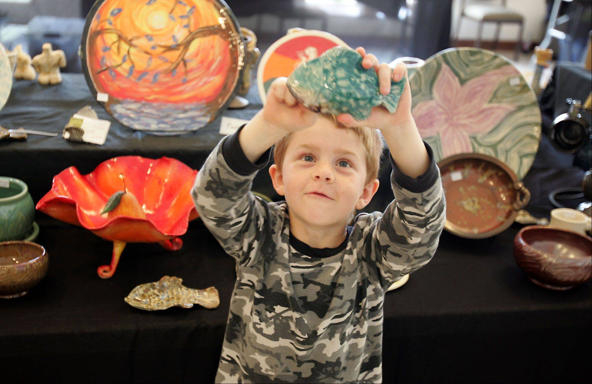 Aidan Kikta, 6, of Romeoville, enjoys holding a ceramic fish, during Cantigny Park's third Ceramic Arts Show.