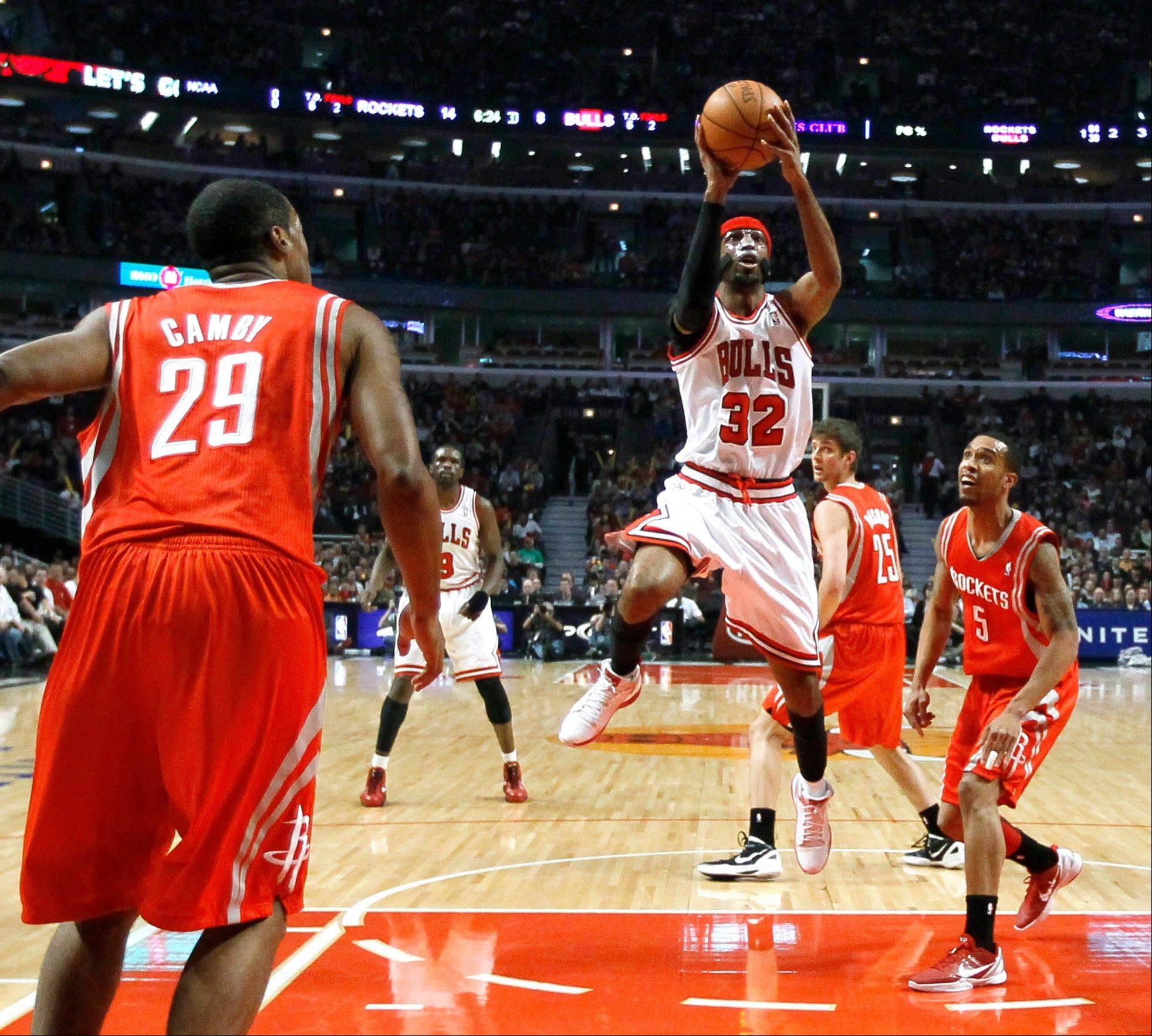 In his first game back after injury, Chicago Bulls guard Richard Hamilton (32) shoots between Houston Rockets center Marcus Camby (29) and guard Courtney Lee during the first half of an NBA basketball game Monday, April 2, 2012, in Chicago.