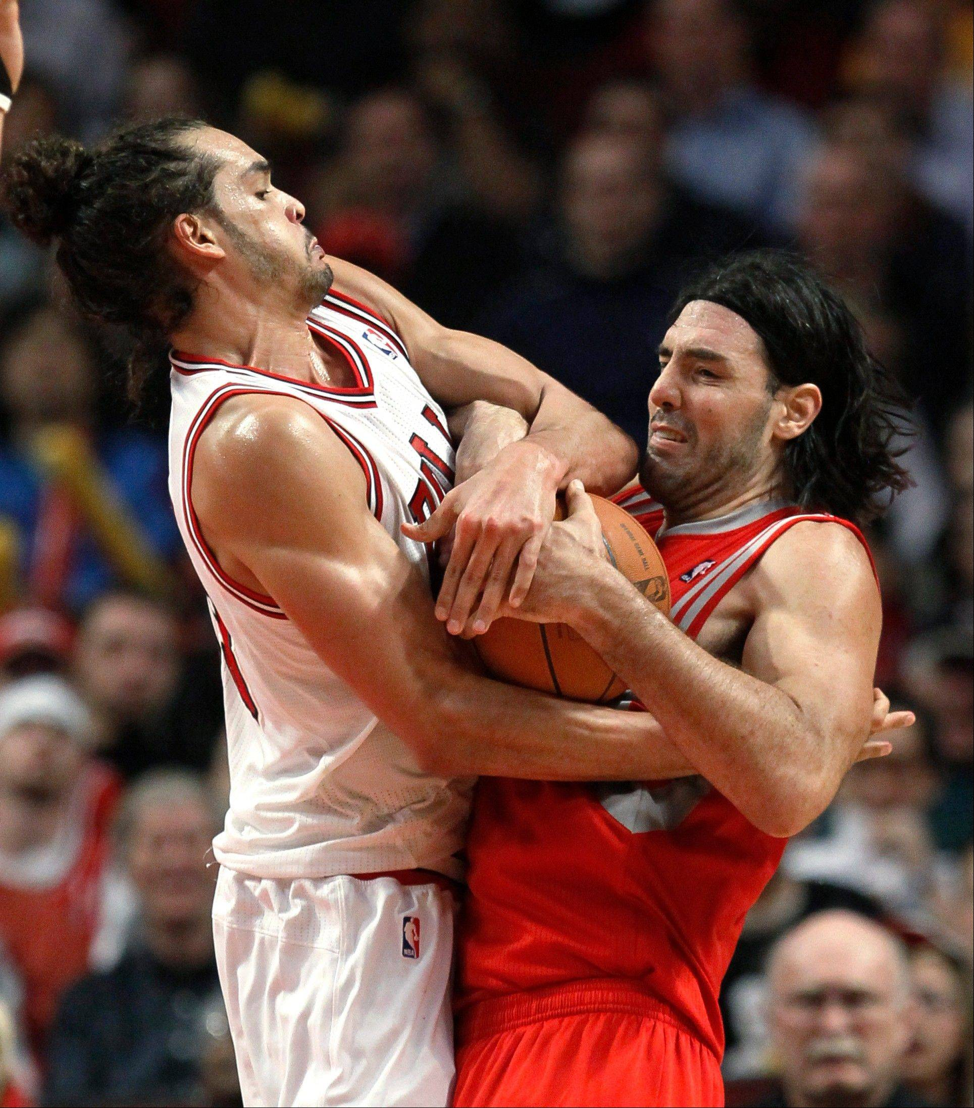 Chicago Bulls center Joakim Noah, left, ties up Houston Rockets forward Luis Scola, resulting in a jump ball, during the second half of an NBA basketball game Monday, April 2, 2012, in Chicago. The Rockets won 99-93.