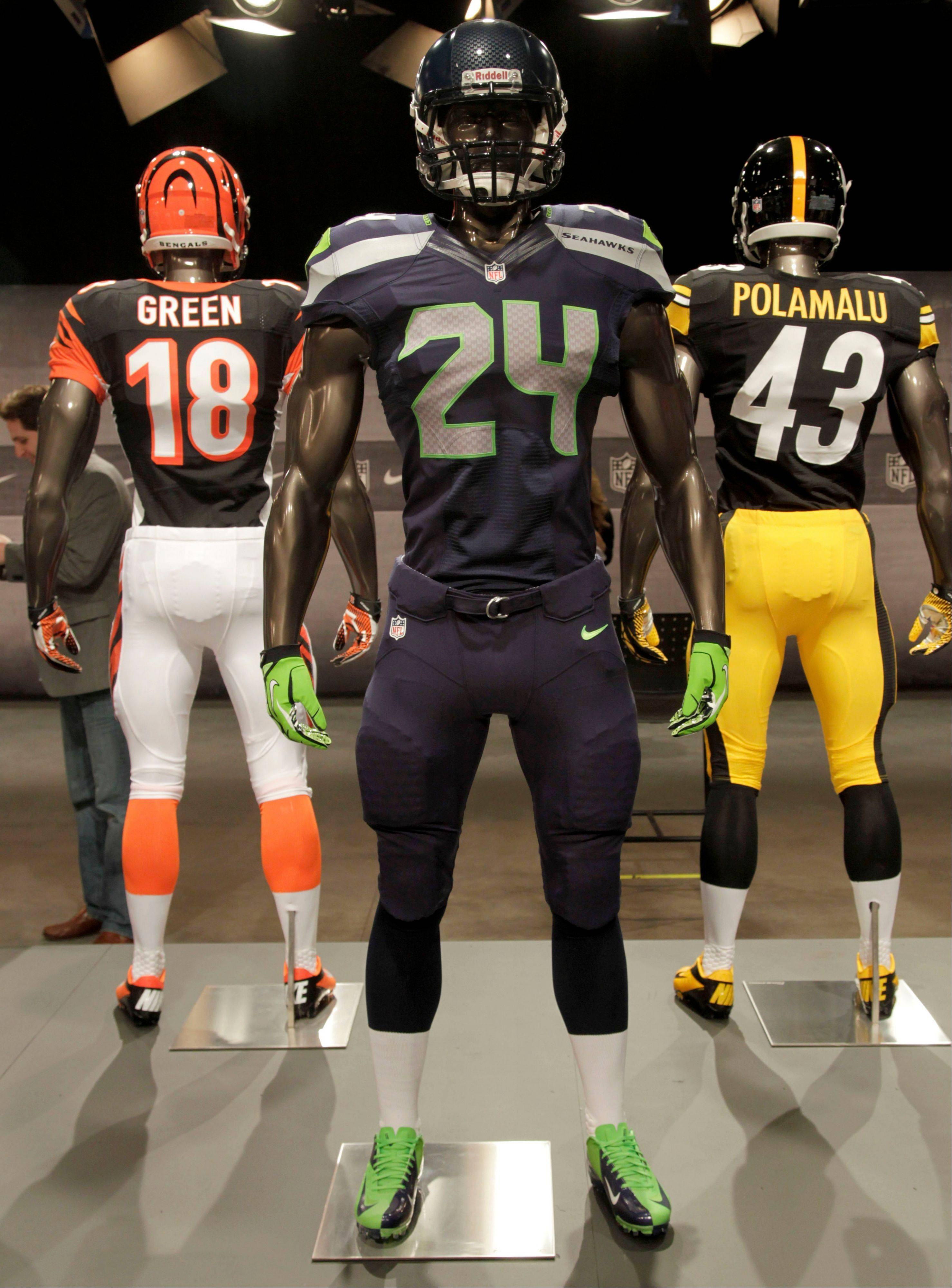 The new Seattle Seahawks uniform, foreground, Pittsburgh Steelers, rear right, and Cincinnati Bengals, rear left, are displayed on mannequins during a presentation in New York, Tuesday, April 3, 2012. The NFL and Nike showed off the new gear in grand style with a gridiron-themed fashion show at a Brooklyn film studio.