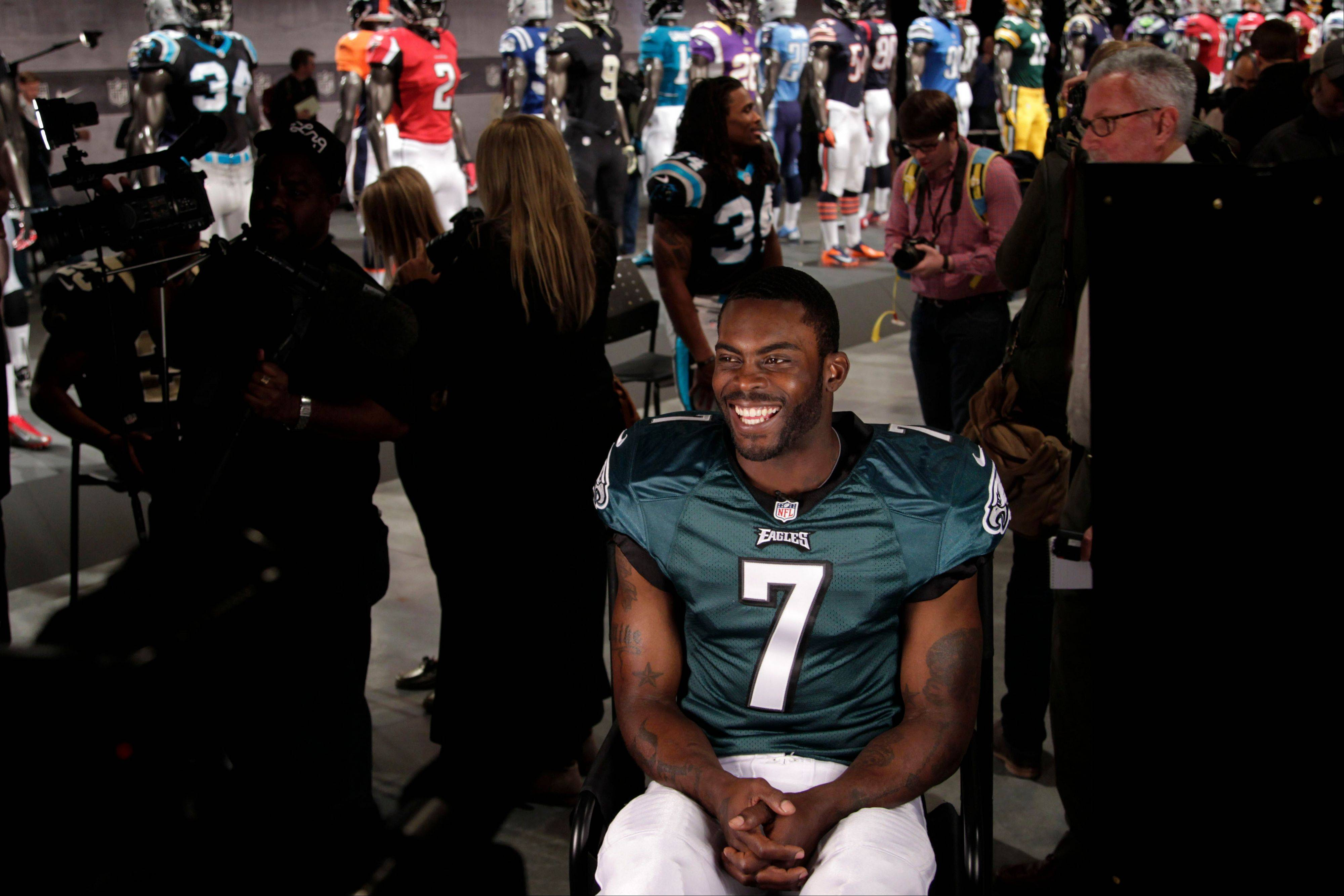 Philadelphia Eagles' Michael Vick smiles before the start of an interview while new uniforms are displayed behind him at a presentation in New York, Tuesday, April 3, 2012. The NFL and Nike showed off the new gear in grand style with a gridiron-themed fashion show at a Brooklyn film studio.