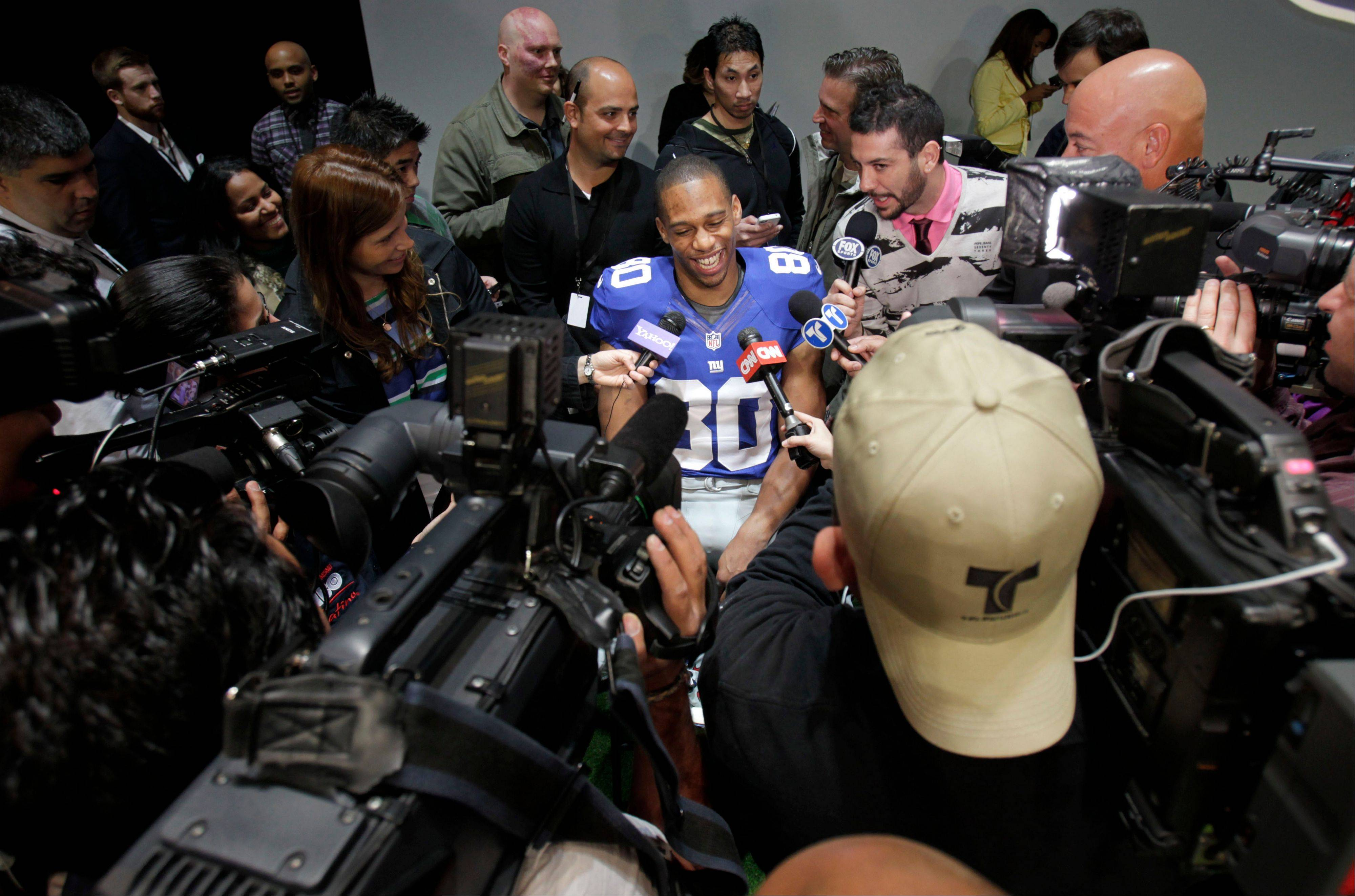 New York Giants' Victor Cruz smiles while surrounded by reporters during a presentation in New York, Tuesday, April 3, 2012. The NFL and Nike showed off the new gear in grand style with a gridiron-themed fashion show at a Brooklyn film studio.