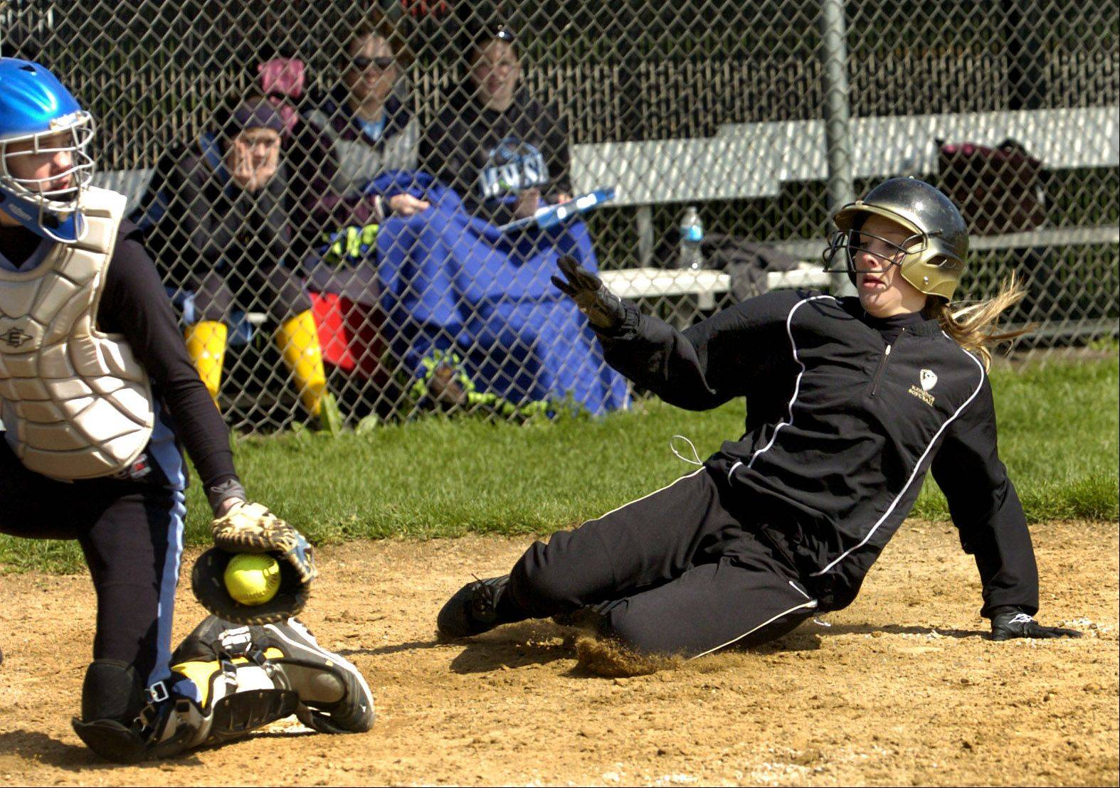 Megan Mertins slides safe into home during Monday's Grayslake North at Maine West softball softball game.