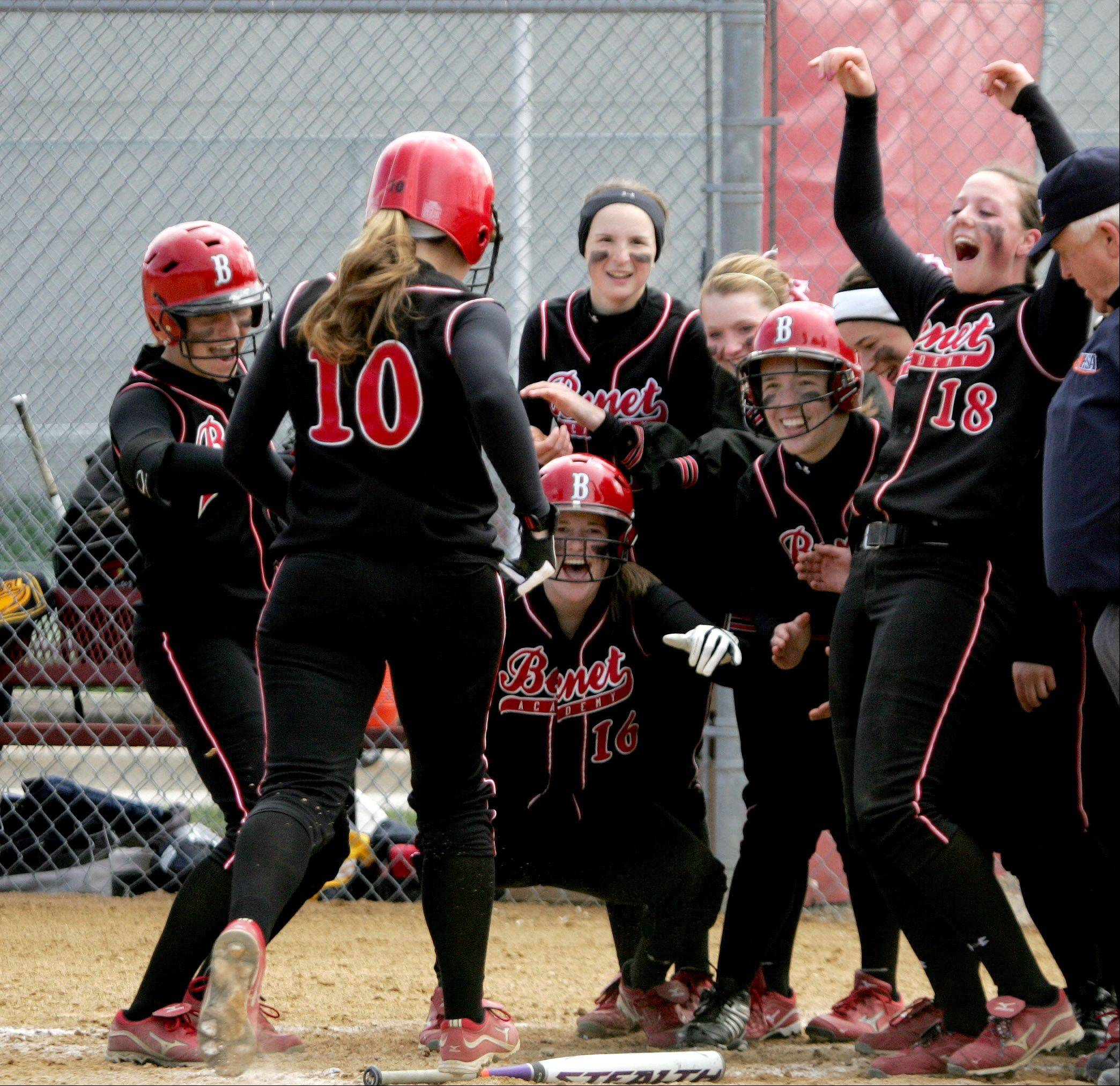 Benet Academy's Kendall Duffy, left, is greeted by her teammates after hitting a home run against Neuqua Valley on Monday in Lisle.