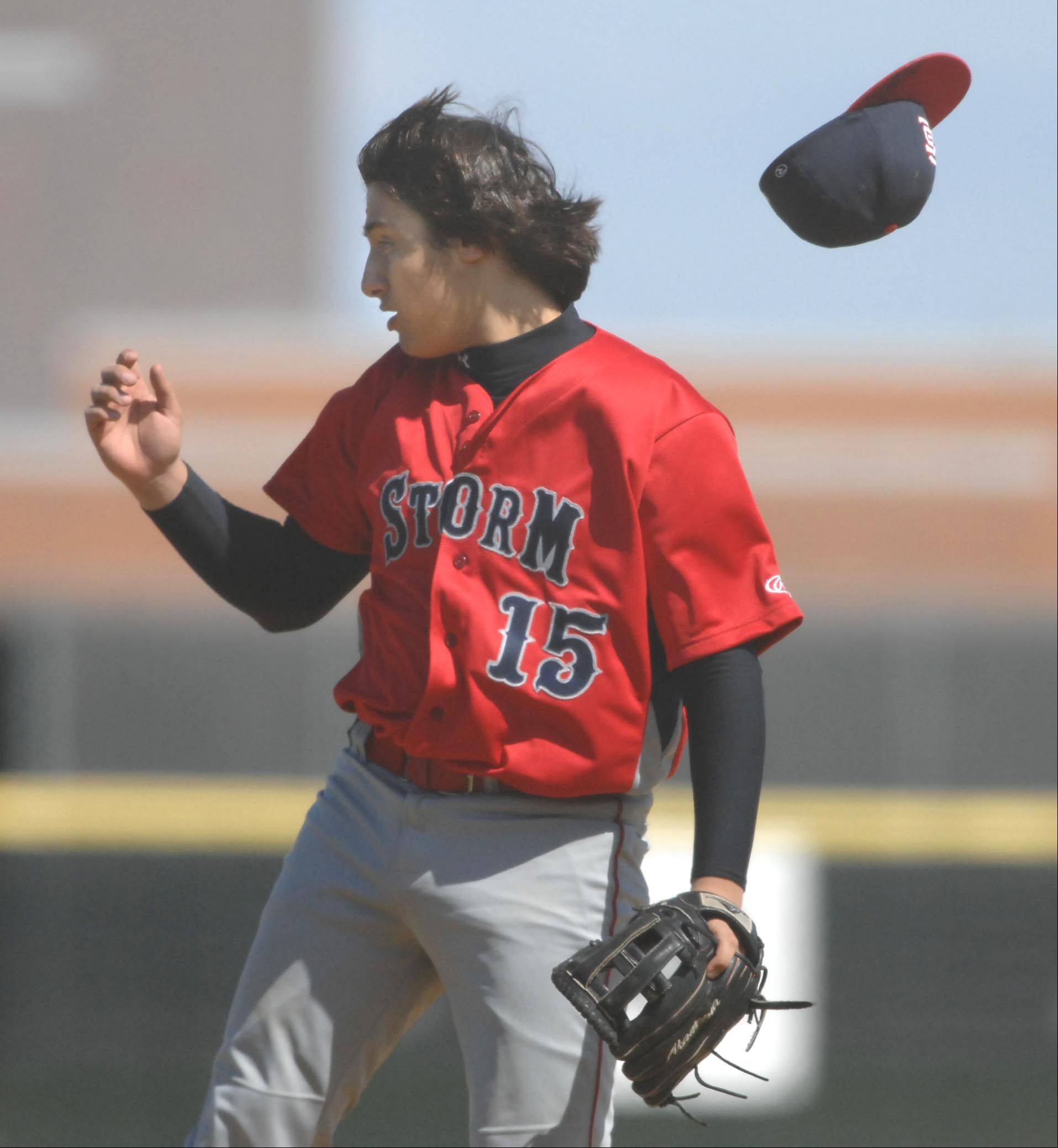 South Elgin pitcher David Palmer loses his hat in the wind Wednesday in Hampshire.