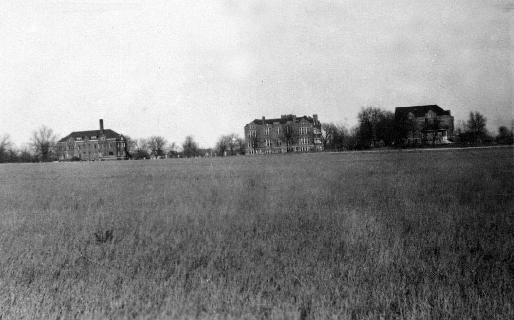 Aurora University's original three buildings, Eckhart Hall, Wilkinson Hall and Davis Hall, rise from a field surrounding the campus. The university celebrated the 100th anniversary of its move from Mendota to Aurora on Wednesday.
