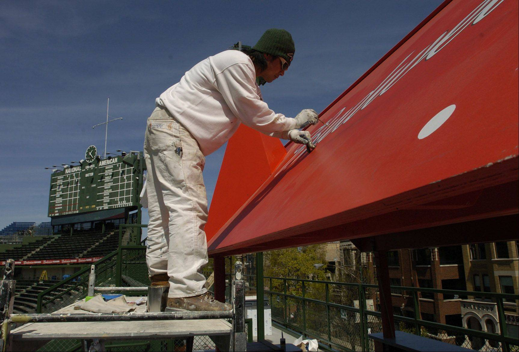 Painter Dante Peralta paints the new Budweiser patio area in right field.